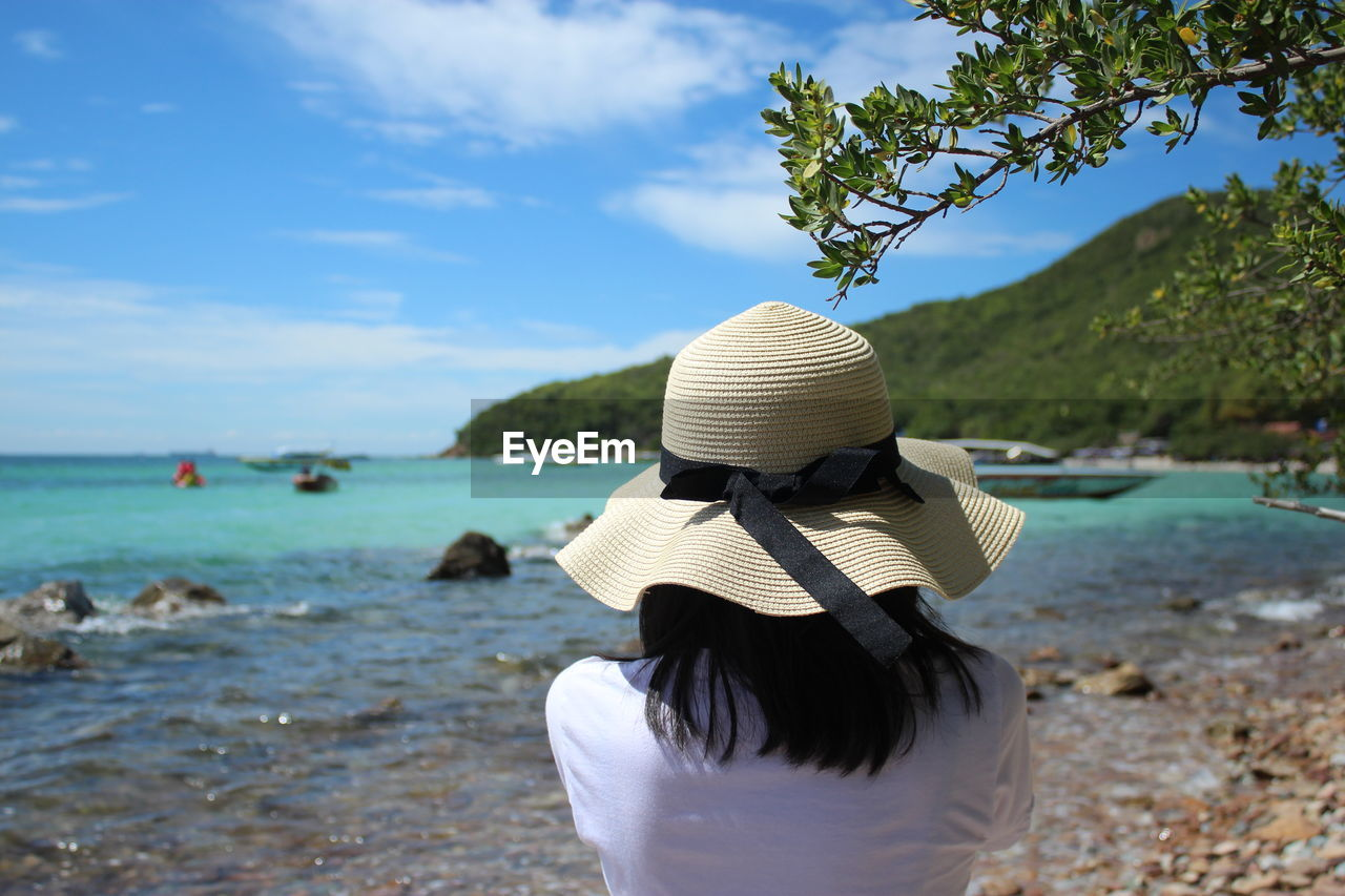 water, hat, rear view, real people, sea, beauty in nature, leisure activity, women, nature, lifestyles, one person, sky, adult, clothing, day, beach, land, outdoors, sun hat, hairstyle