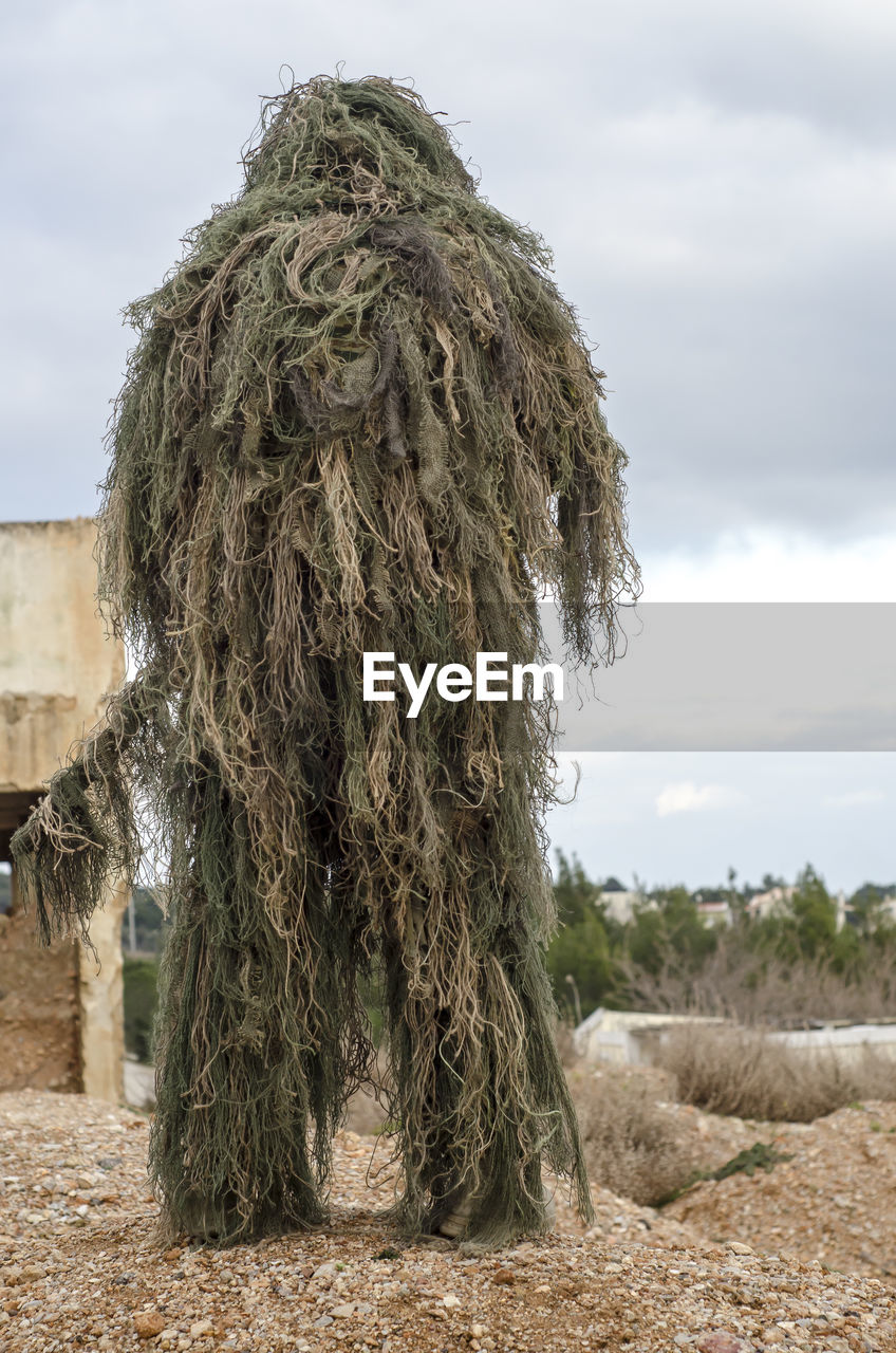 Rear View Of Army Man Wearing Ghillie Suit On Field