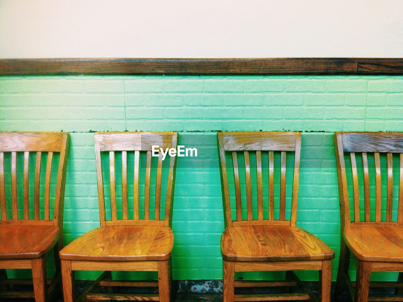 Empty Wooden Chairs Against Green Wall