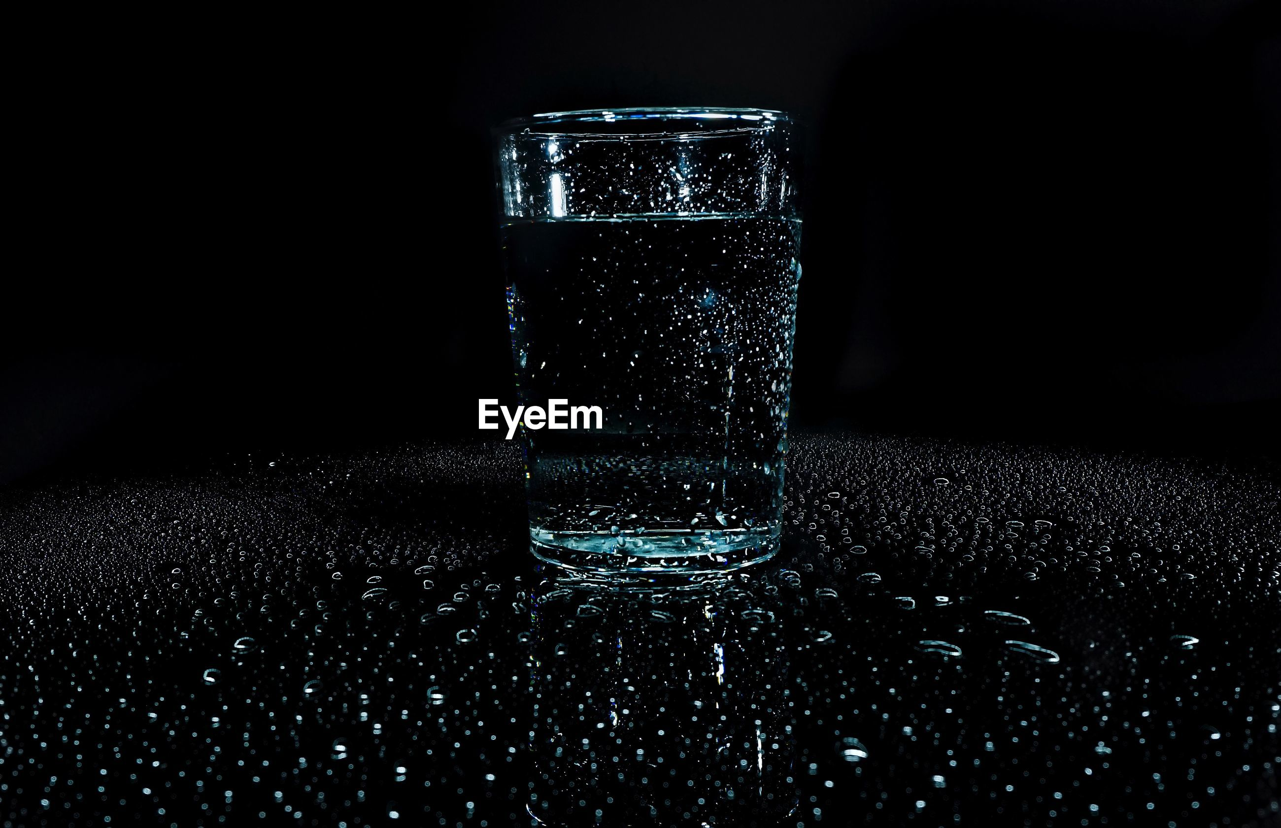 indoors, night, illuminated, dark, glass - material, close-up, transparent, lighting equipment, black background, glass, no people, window, copy space, darkroom, reflection, table, light, light - natural phenomenon, pattern, glowing