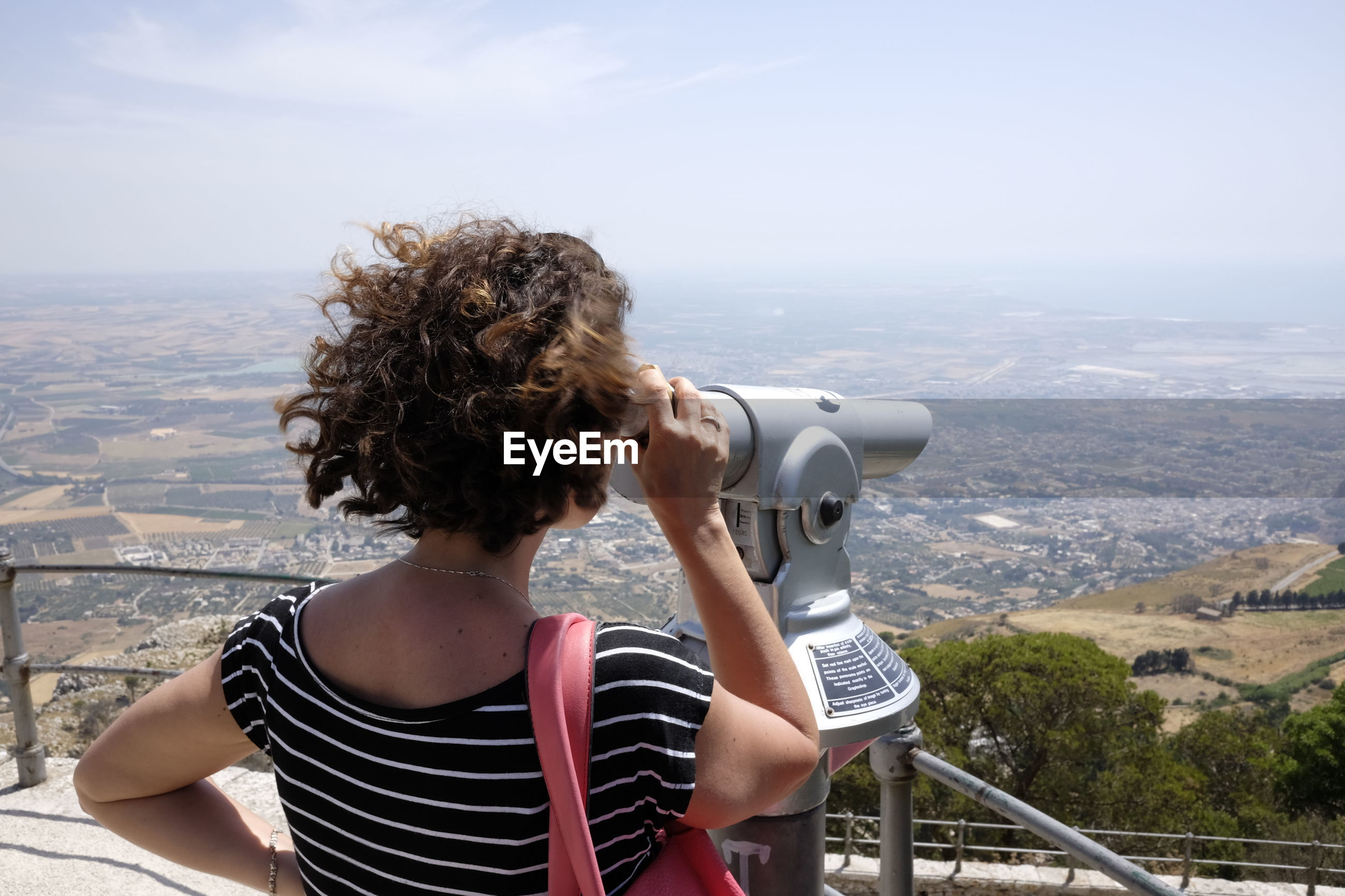 Rear view of woman looking through coin-operated binoculars from observation point at erice