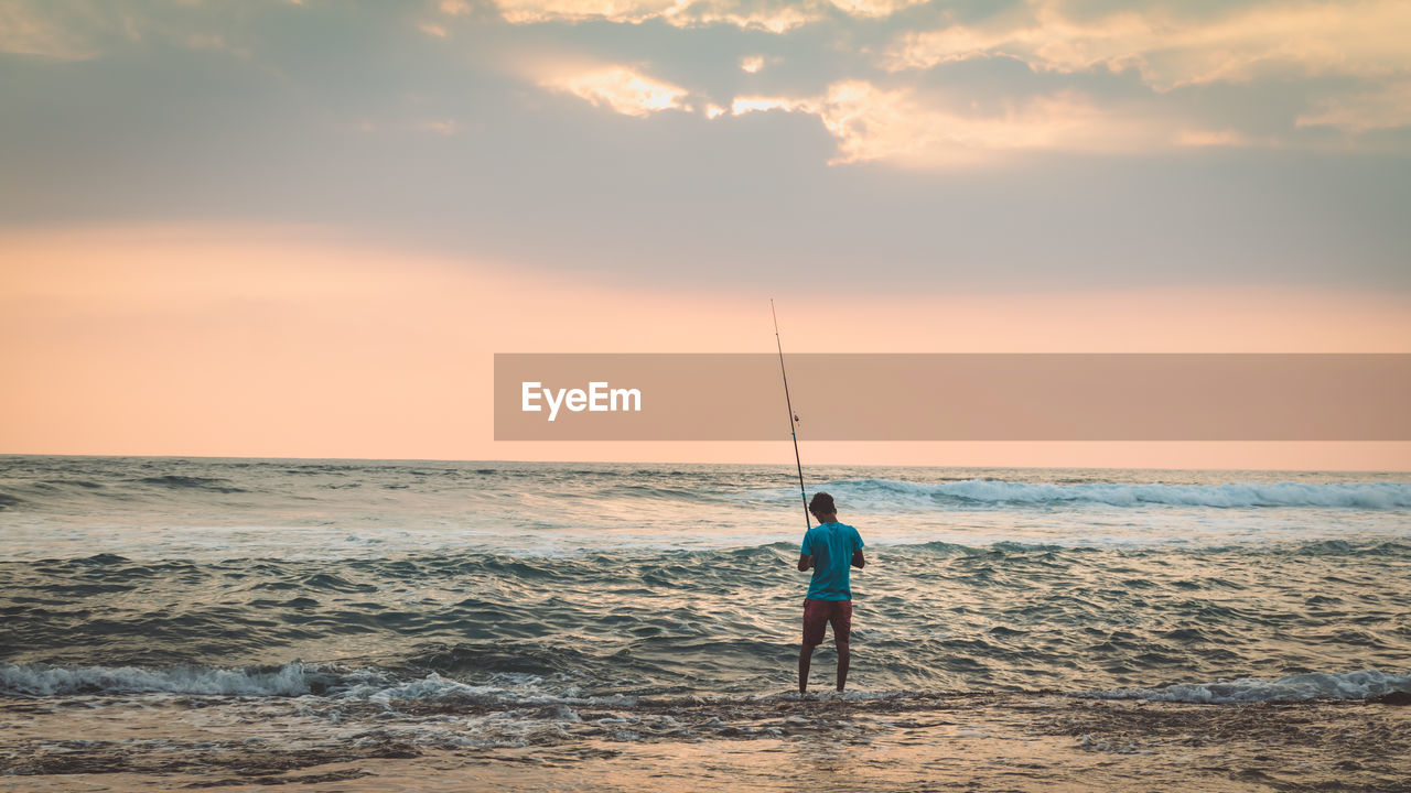 Rear view of man fishing in sea against sky during sunset