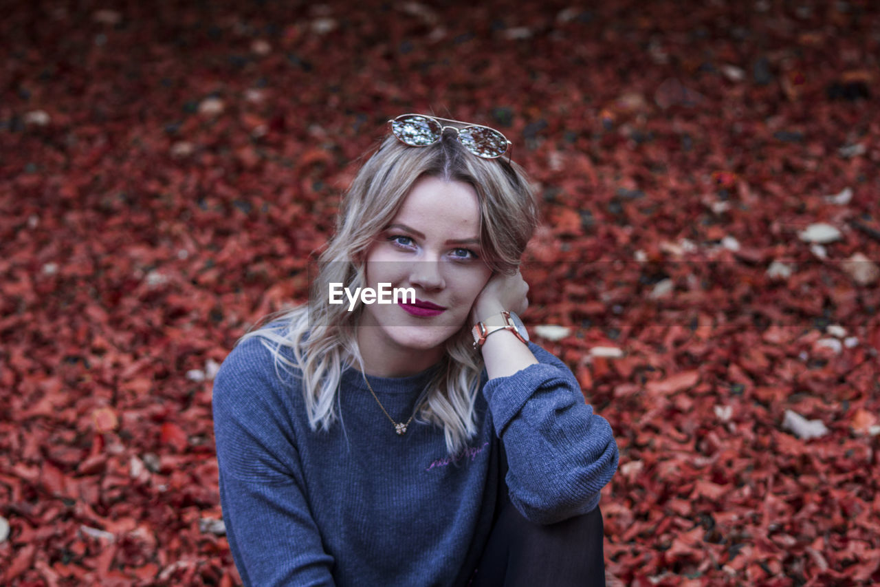 Portrait of young woman against autumn leaves