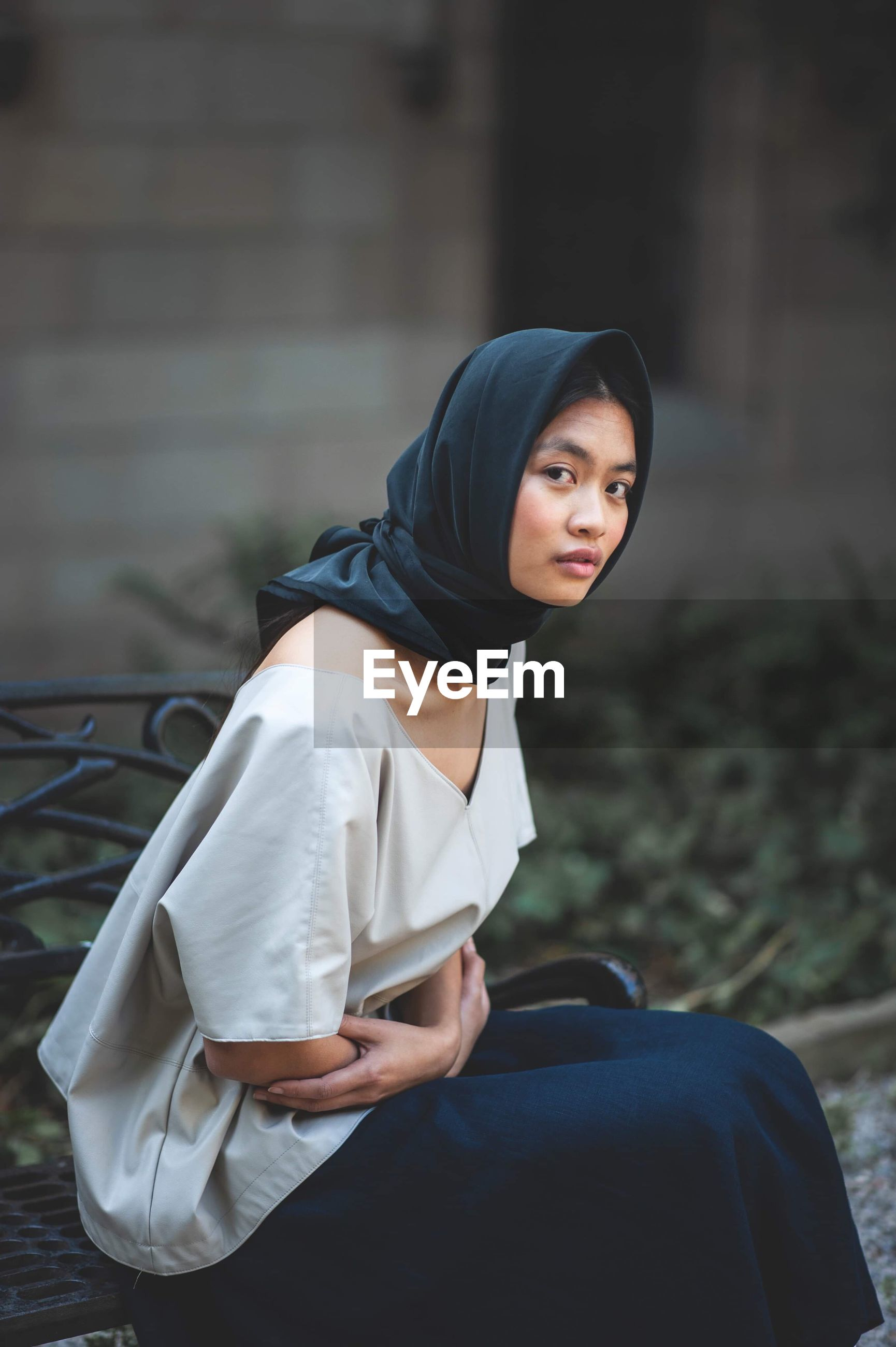 real people, one person, lifestyles, focus on foreground, sitting, three quarter length, leisure activity, young adult, clothing, day, casual clothing, looking, outdoors, side view, portrait, looking away, women, adult, contemplation, teenager, hood - clothing, hairstyle