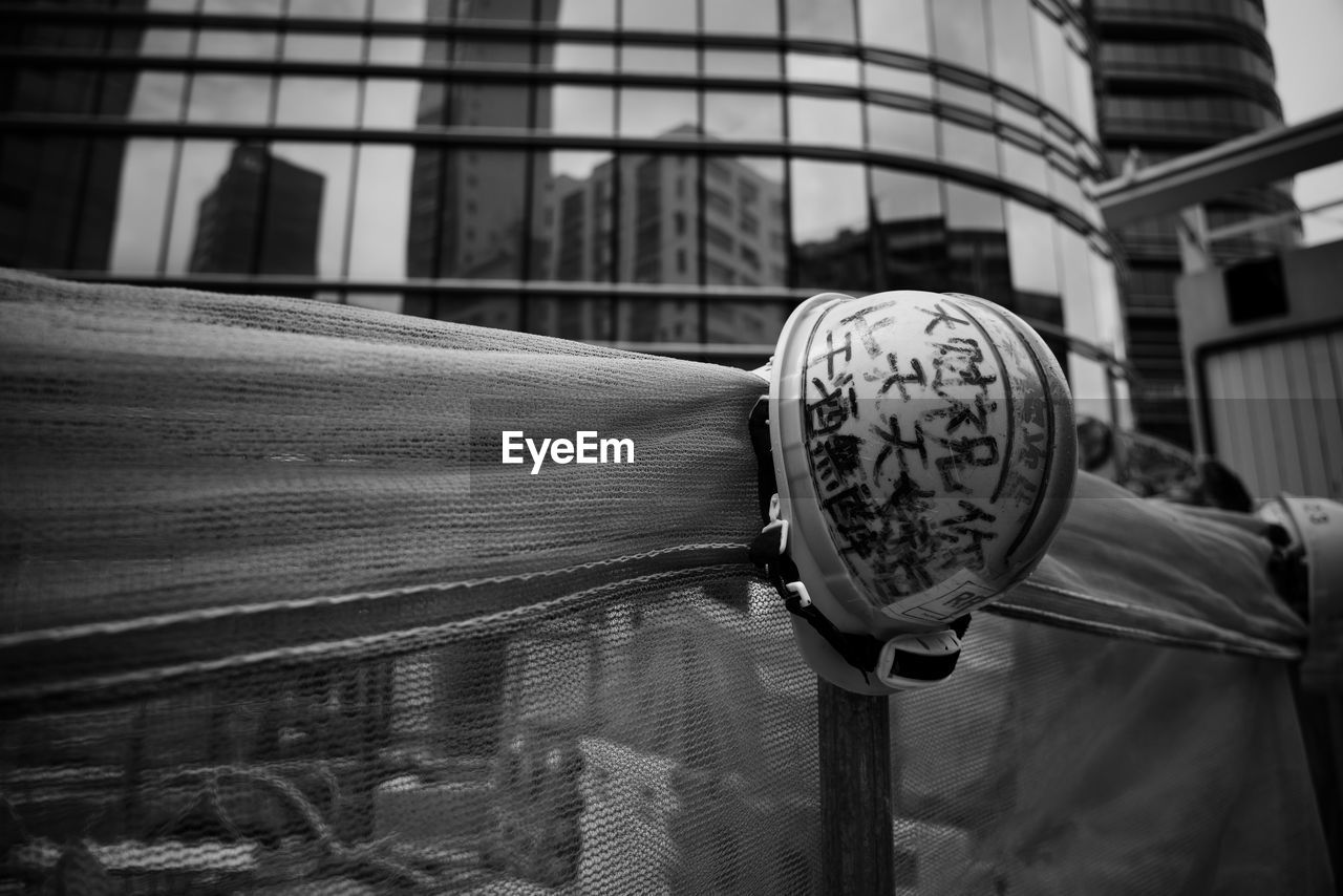 built structure, focus on foreground, architecture, building exterior, day, one person, close-up, building, city, real people, outdoors, metal, art and craft, lifestyles, reflection, pattern, railing