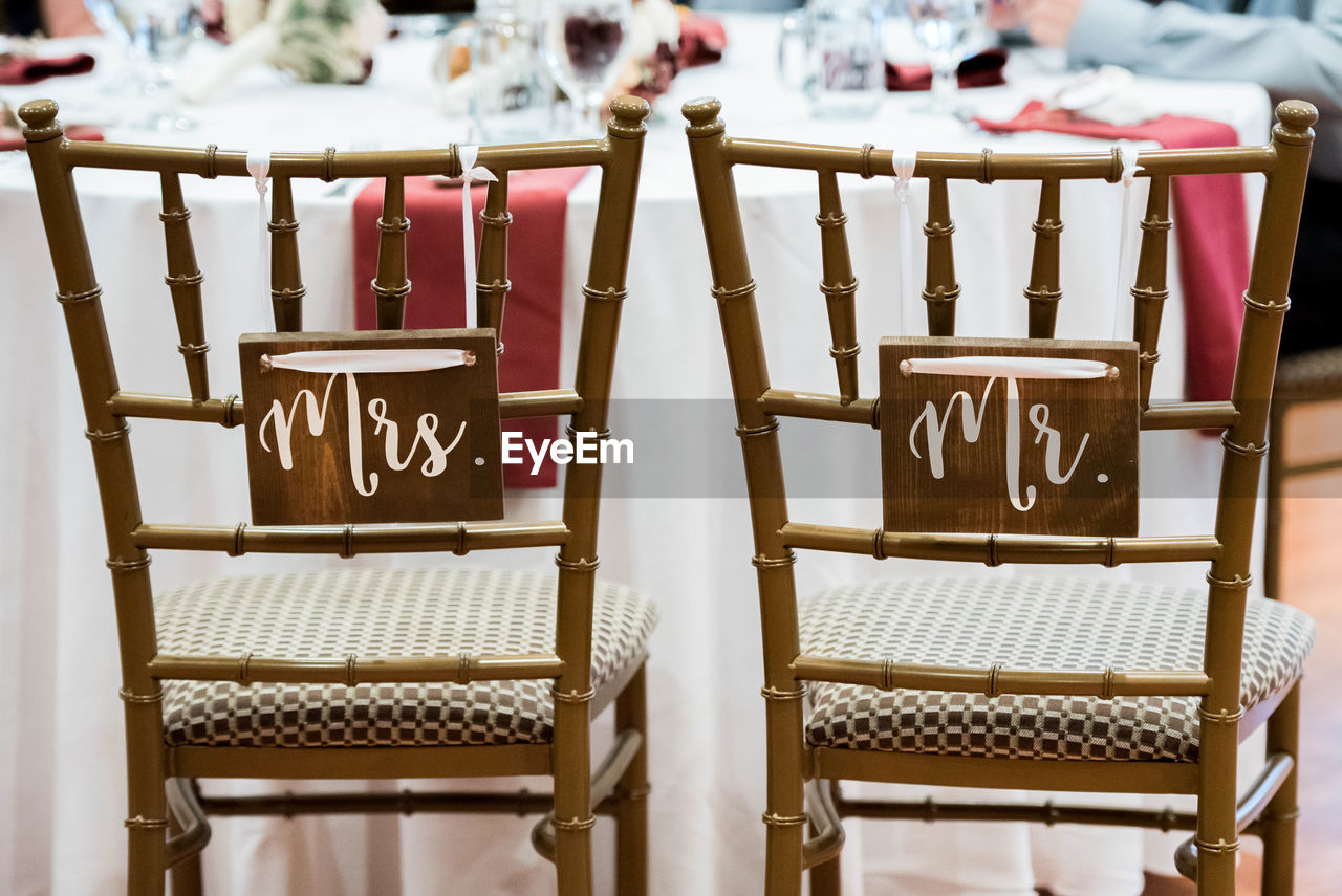 text, communication, seat, focus on foreground, chair, no people, western script, day, table, wood - material, script, non-western script, indoors, close-up, still life, sign, arrangement, hanging, pattern, group