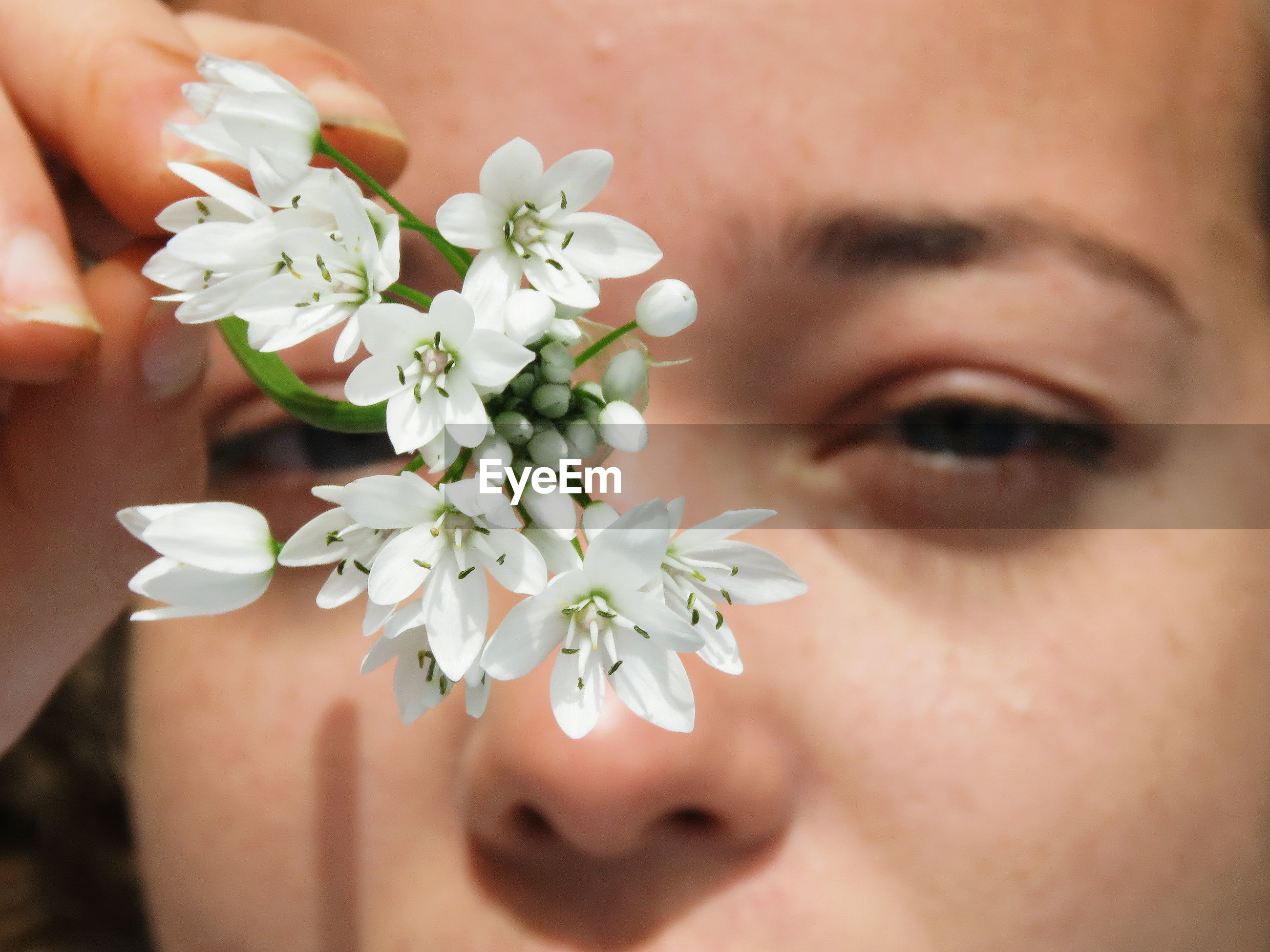 Close-up portrait of woman holding white flowers