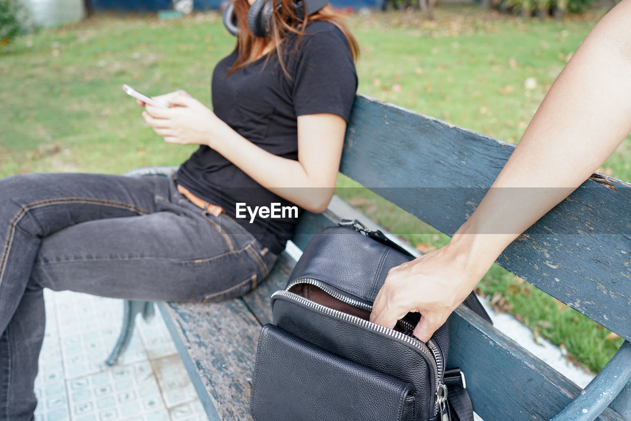 Mugger stealing from bag while woman using mobile phone on bench