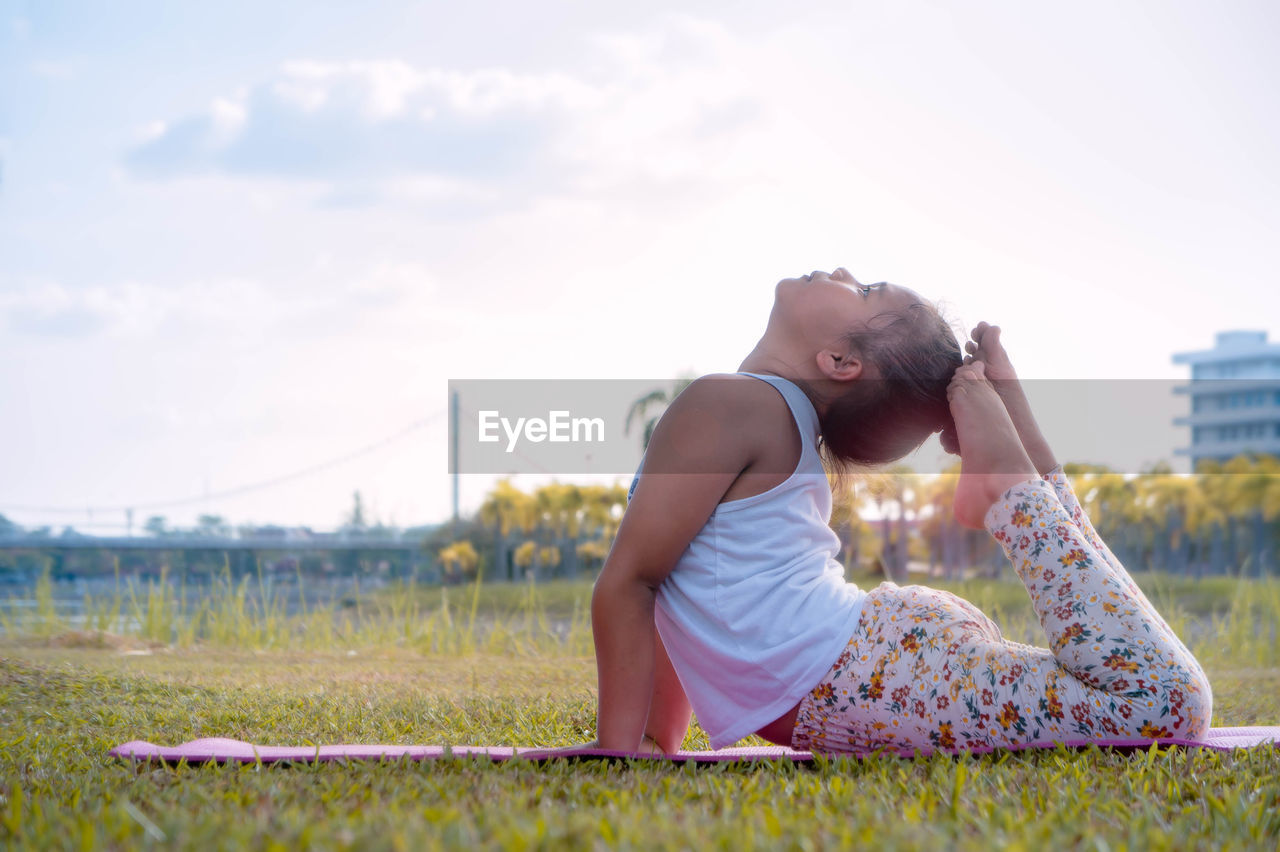 Side View Of Girl Practicing Yoga At Park Against Sky