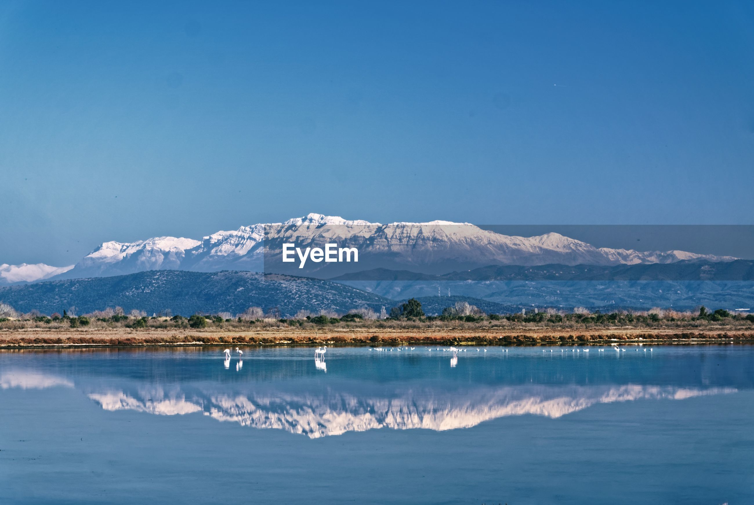Scenic view of lake and snowcapped mountains against clear blue sky