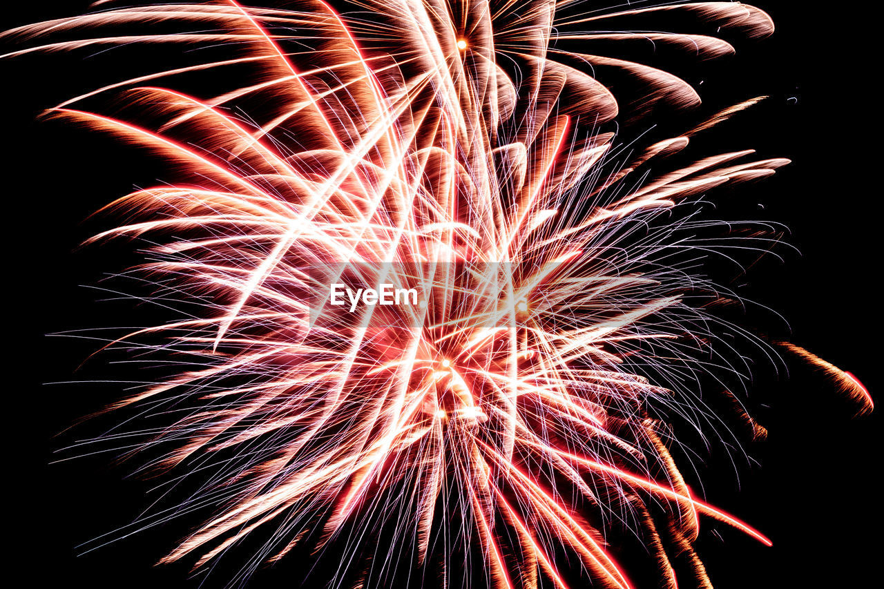 night, firework display, firework - man made object, celebration, arts culture and entertainment, exploding, illuminated, low angle view, long exposure, motion, multi colored, human hand, sky, black background, outdoors, people