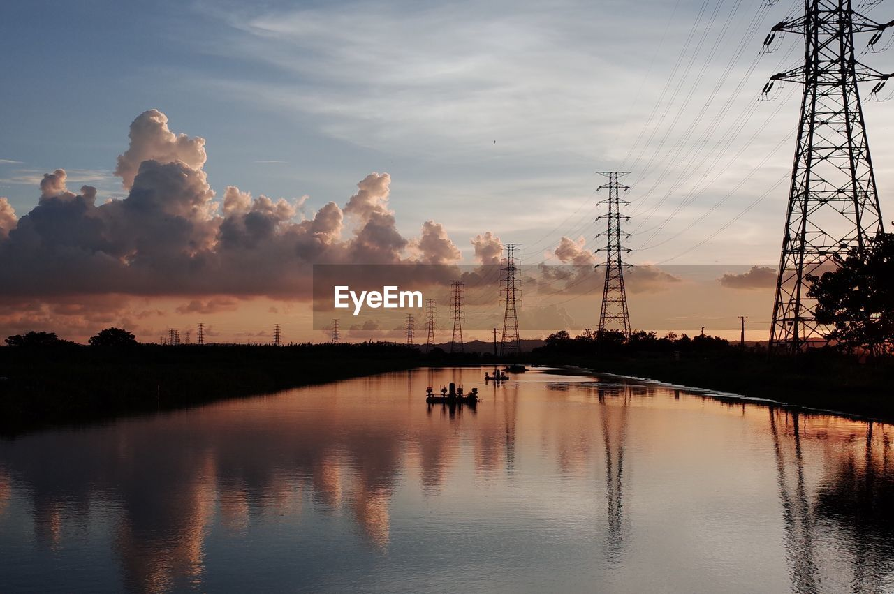 Reflection Of Electricity Pylons Against Sky On Lake During Sunset
