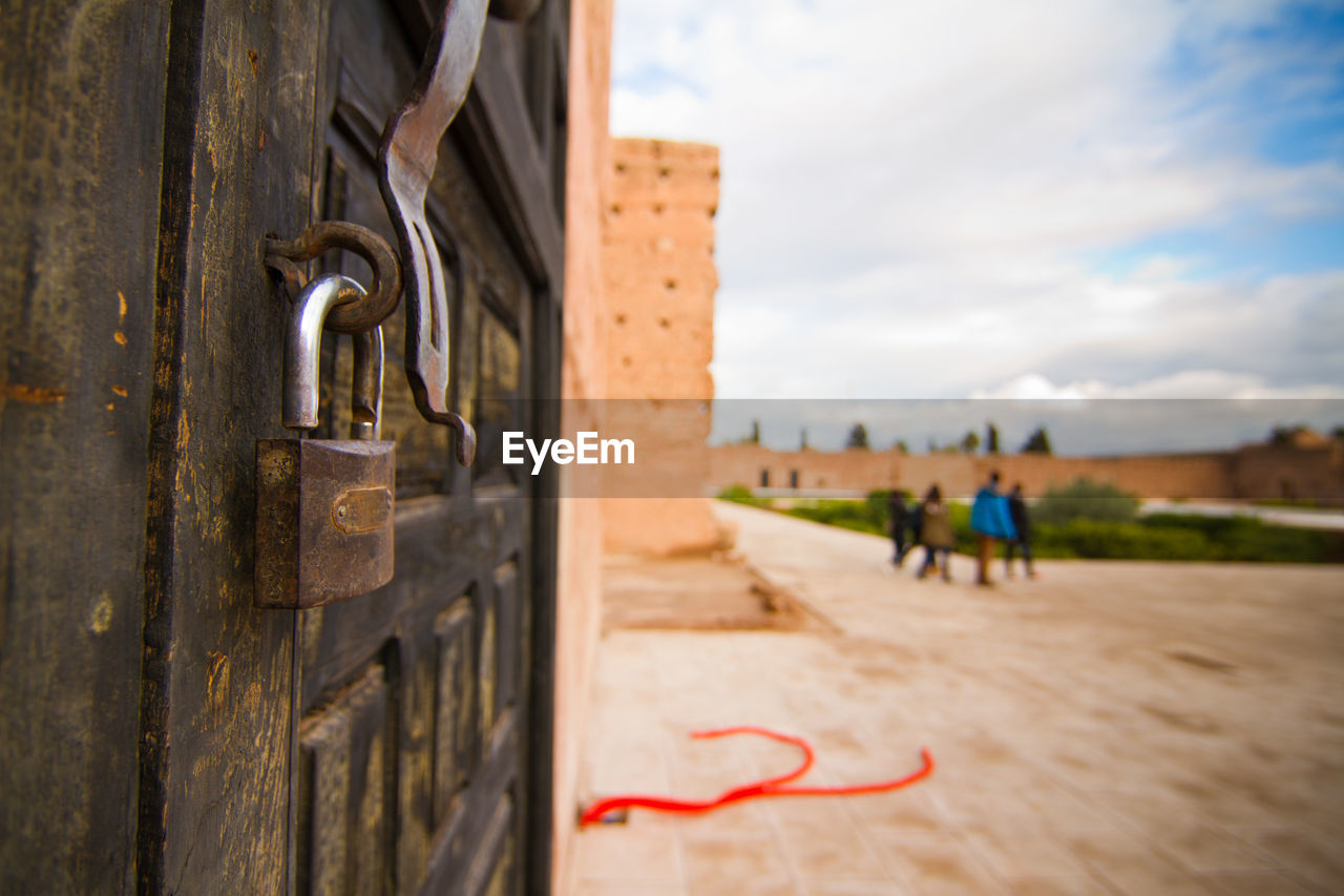 security, metal, safety, protection, day, architecture, focus on foreground, wood - material, lock, close-up, built structure, incidental people, selective focus, outdoors, cloud - sky, real people, entrance, padlock, sky, men