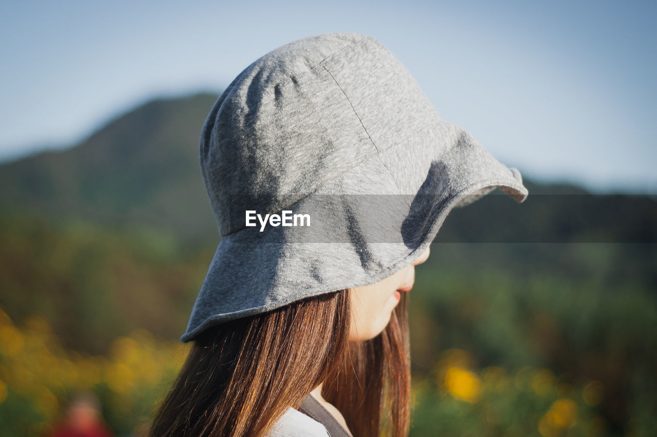 Side View Of Woman Wearing Hat Against Sky