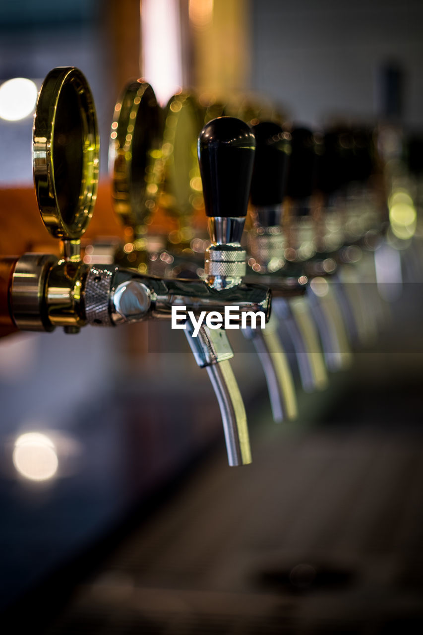 drink, refreshment, food and drink, alcohol, selective focus, no people, bar counter, beer - alcohol, glass, indoors, close-up, in a row, bar - drink establishment, beer, beer tap, focus on foreground, household equipment, drinking glass, bottle, business, craft beer