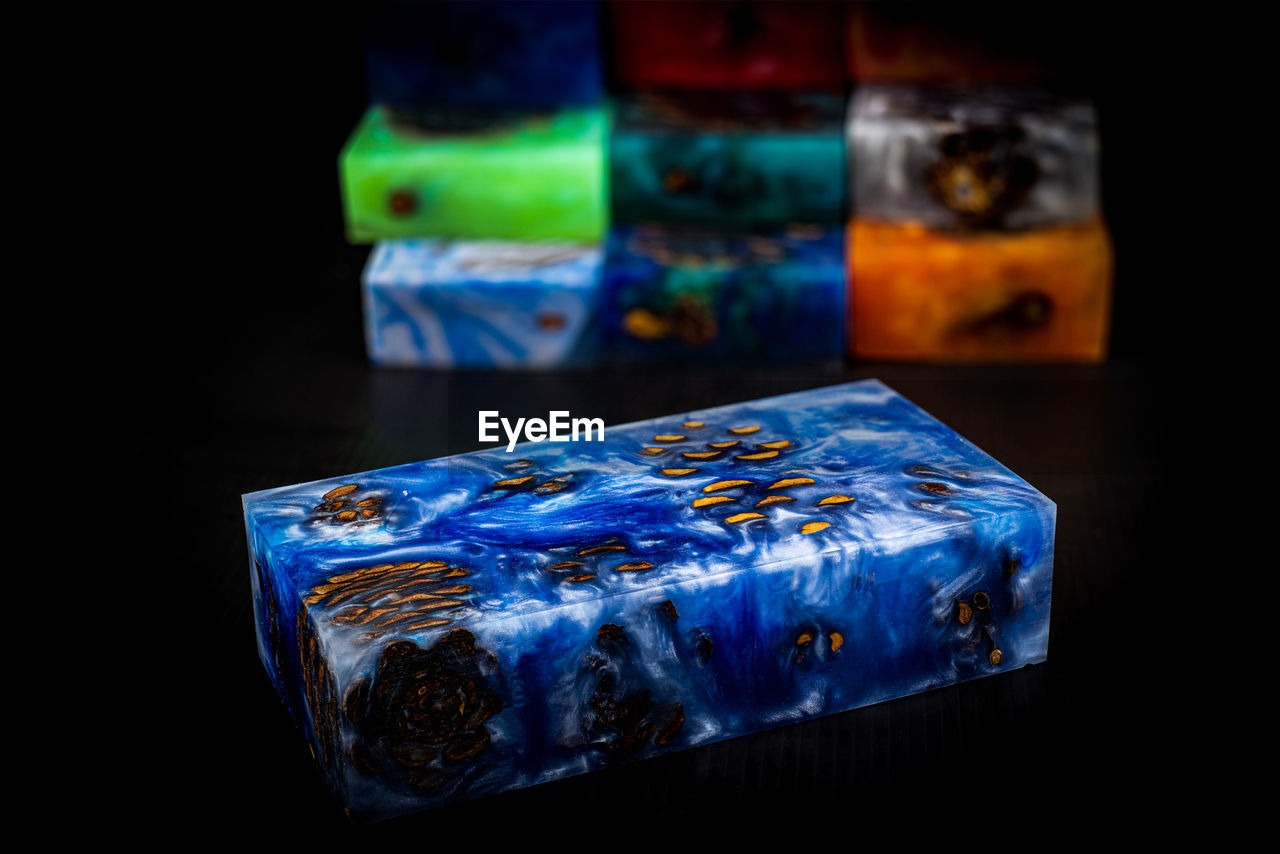 indoors, blue, close-up, no people, table, still life, studio shot, multi colored, black background, food and drink, container, focus on foreground, cold temperature, cube shape, glass - material, transparent, freshness, ice cube, food, glass, melting