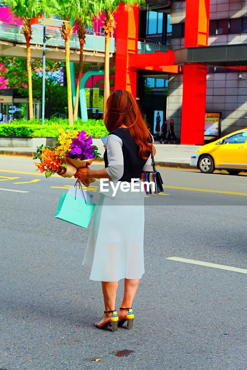 real people, city, full length, one person, women, architecture, lifestyles, road, transportation, street, flower, flowering plant, leisure activity, females, adult, walking, standing, motor vehicle, built structure, outdoors, hairstyle