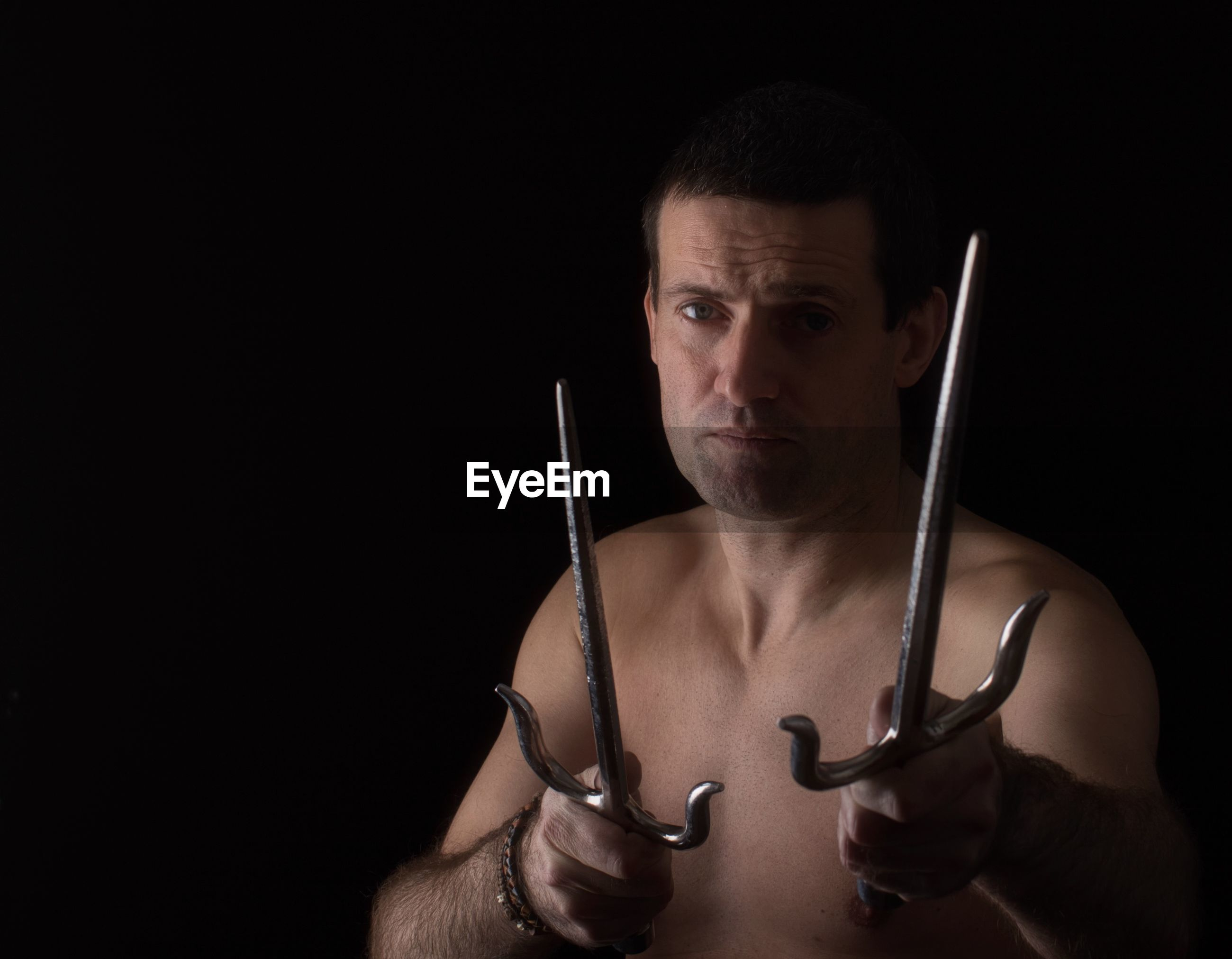 Portrait of shirtless man holding swords over black background