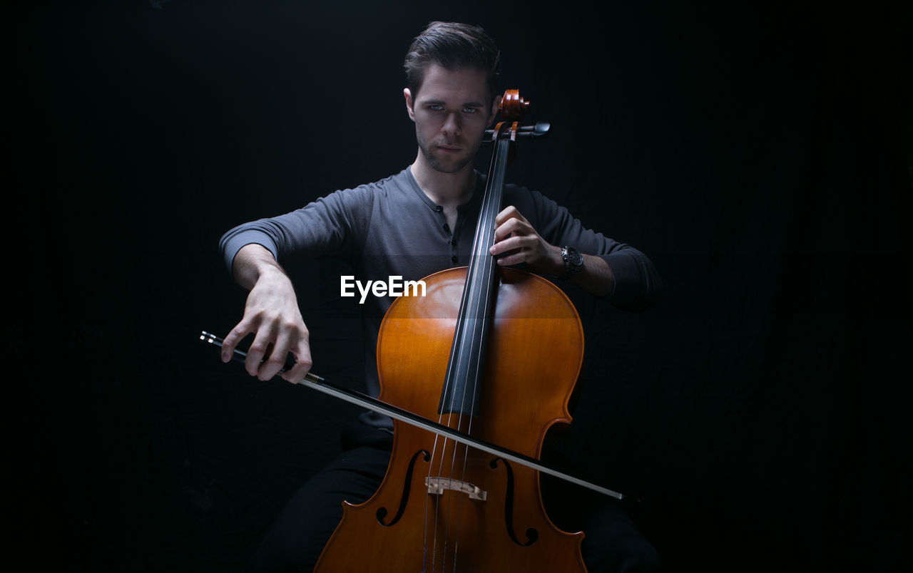 music, musical instrument, string instrument, one person, arts culture and entertainment, musical equipment, musician, playing, artist, black background, young adult, indoors, front view, bow - musical equipment, performance, holding, studio shot, young men, cello, skill, cellist
