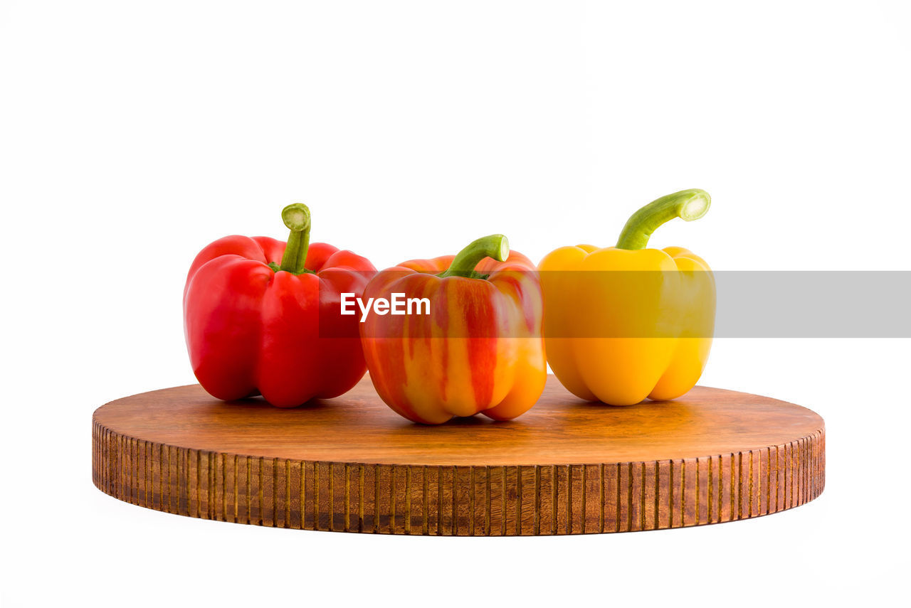 Close-up of bell peppers on wooden plate against white background