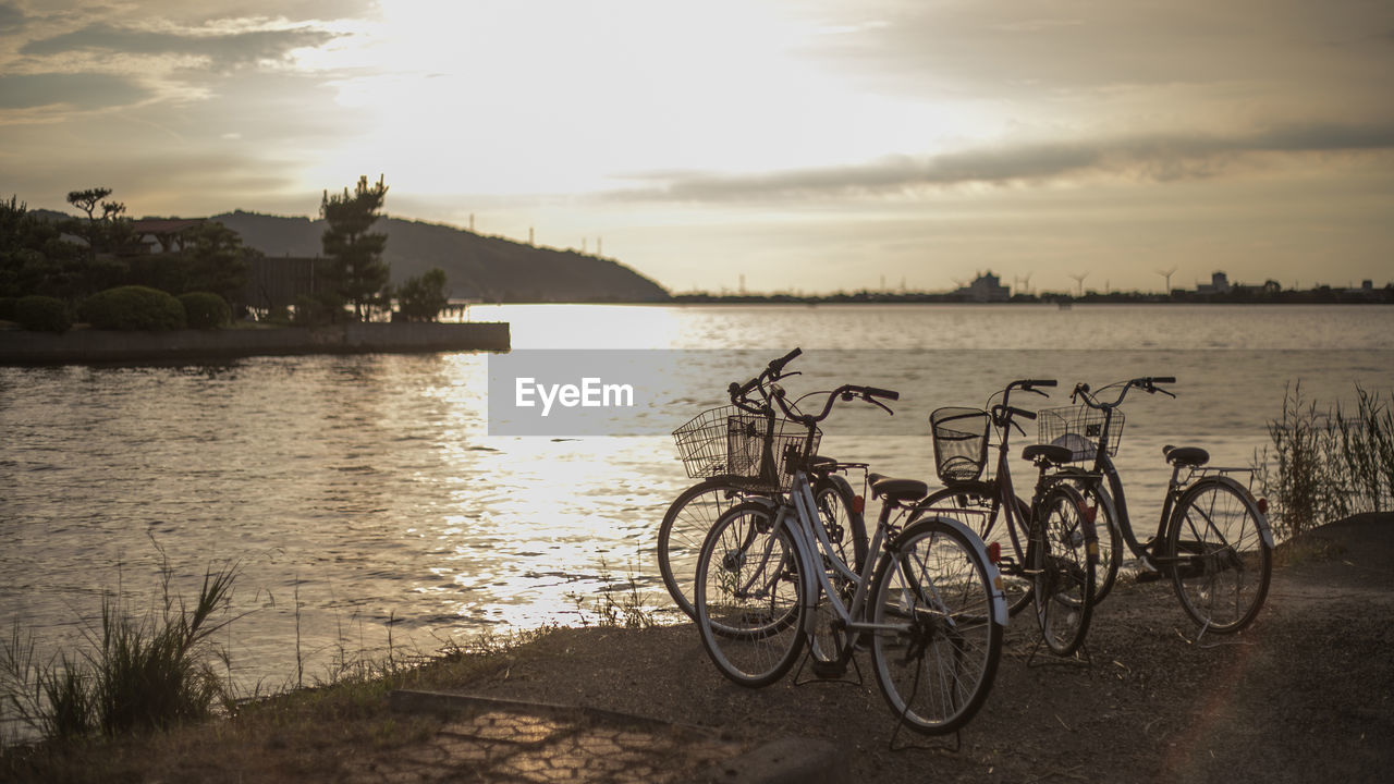 water, sky, bicycle, transportation, cloud - sky, nature, mode of transportation, sunset, tree, land vehicle, plant, no people, tranquility, river, stationary, tranquil scene, beauty in nature, scenics - nature, outdoors