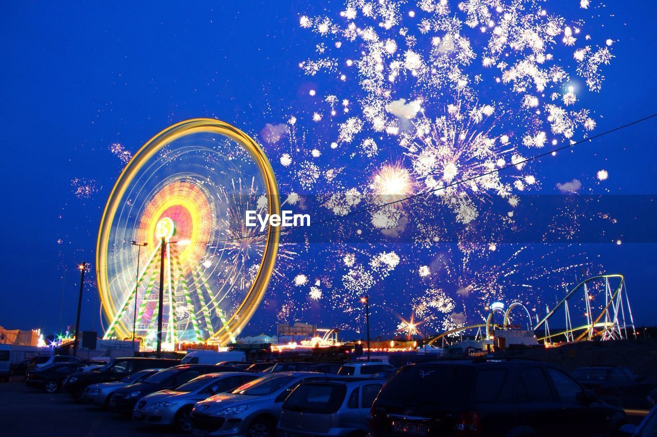 Illuminated ferris wheel against blue sky with parked cars in foreground