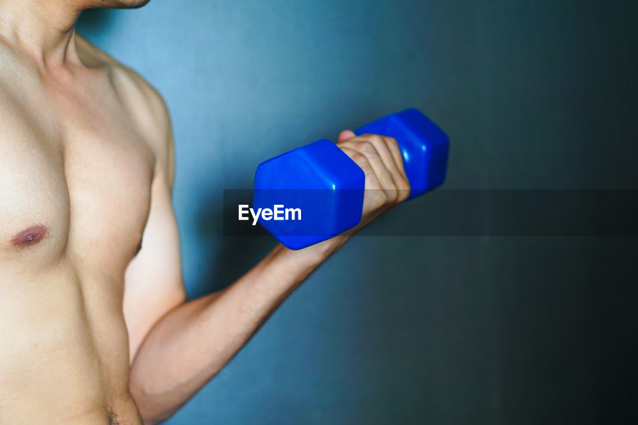 Midsection of shirtless muscular man holding blue dumbbell at home