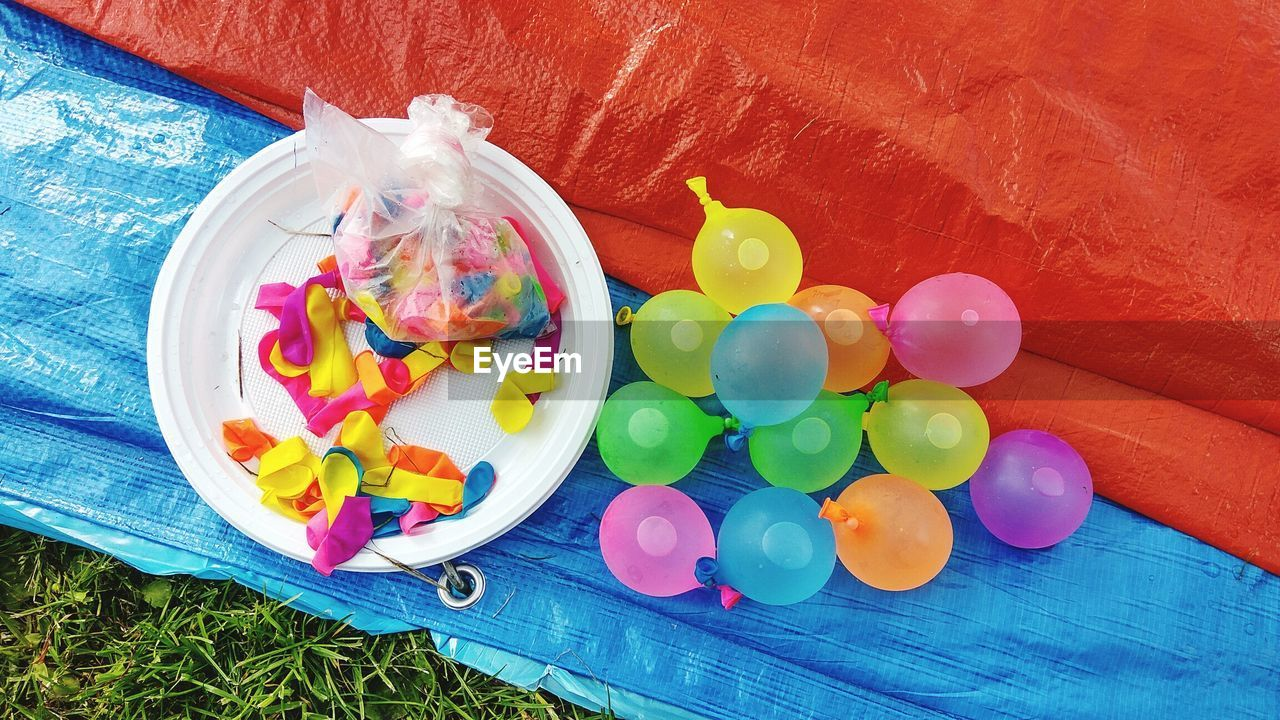 Directly above shot of water bombs and balloons on tarpaulin