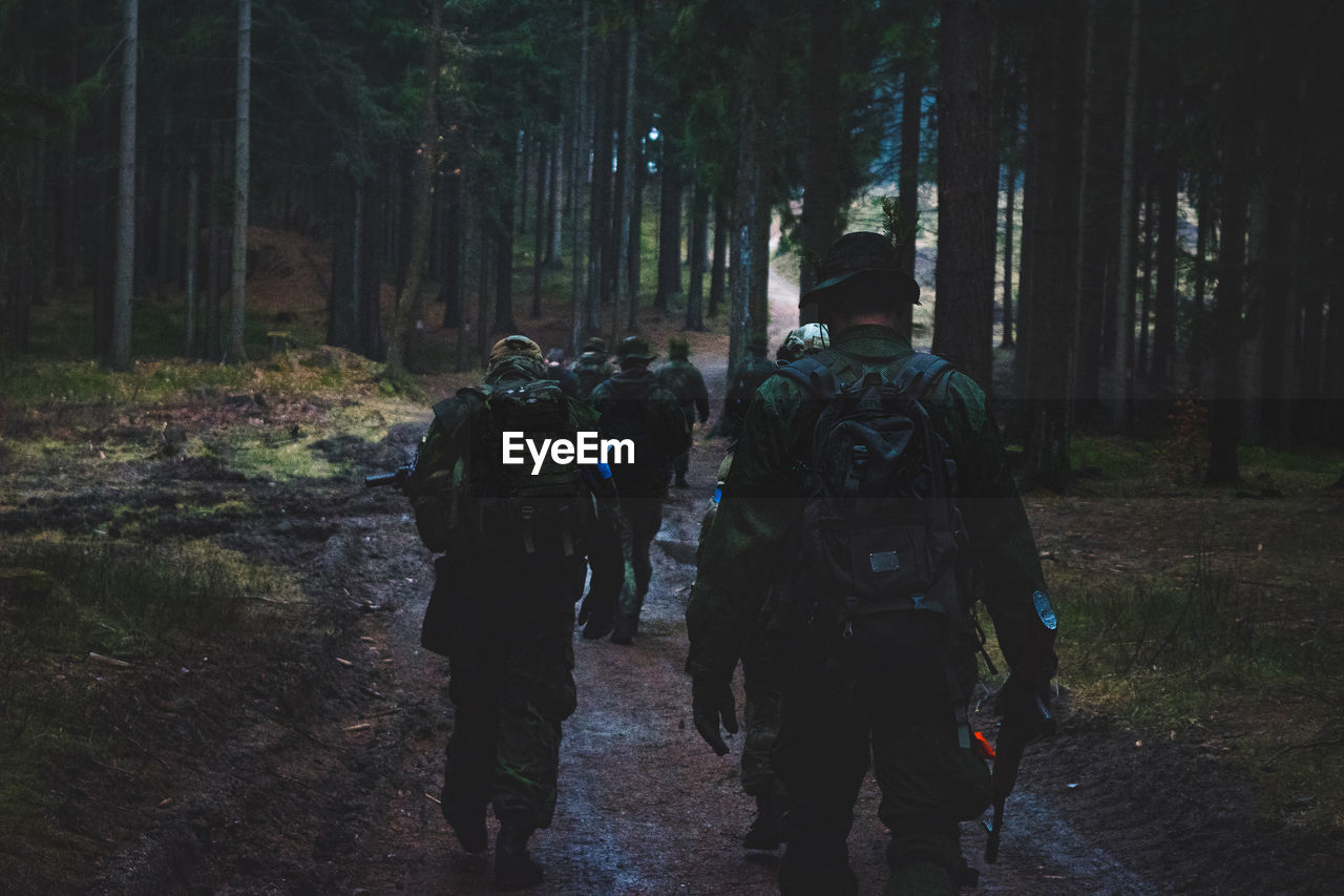 Rear View Of Soldiers Walking In Forest