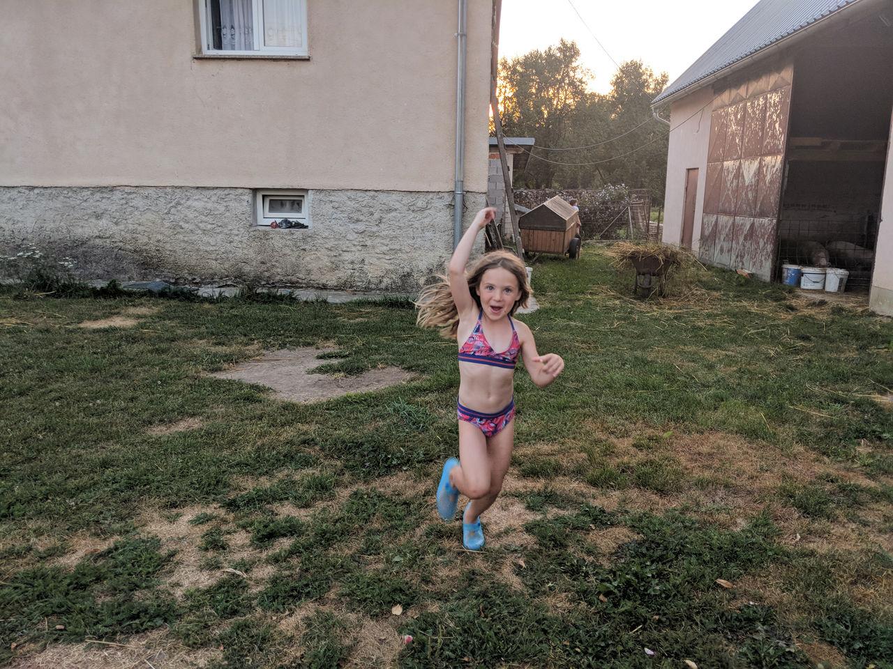 FULL LENGTH OF A GIRL STANDING AGAINST BUILDING