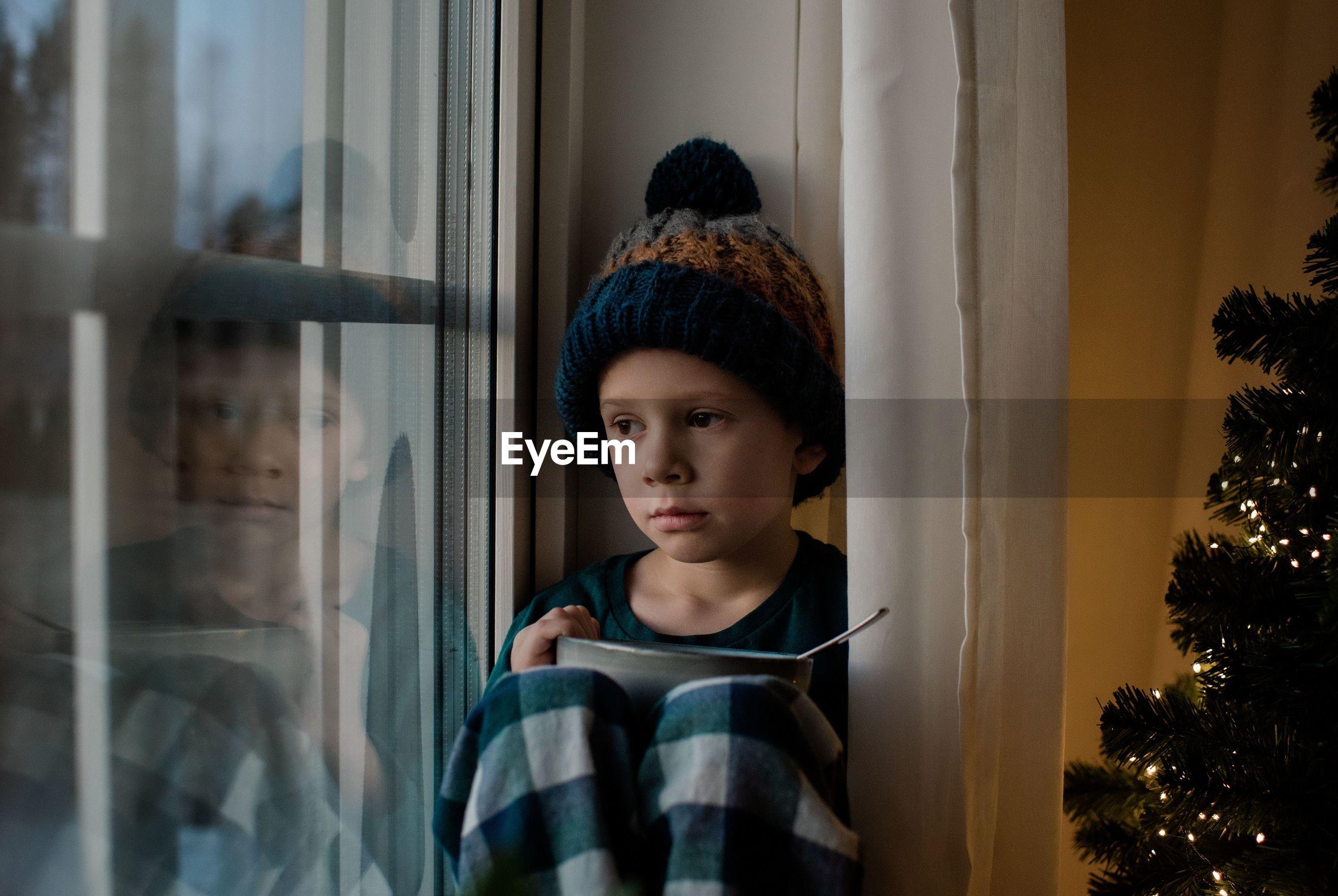 PORTRAIT OF BOY LOOKING AT WINDOW