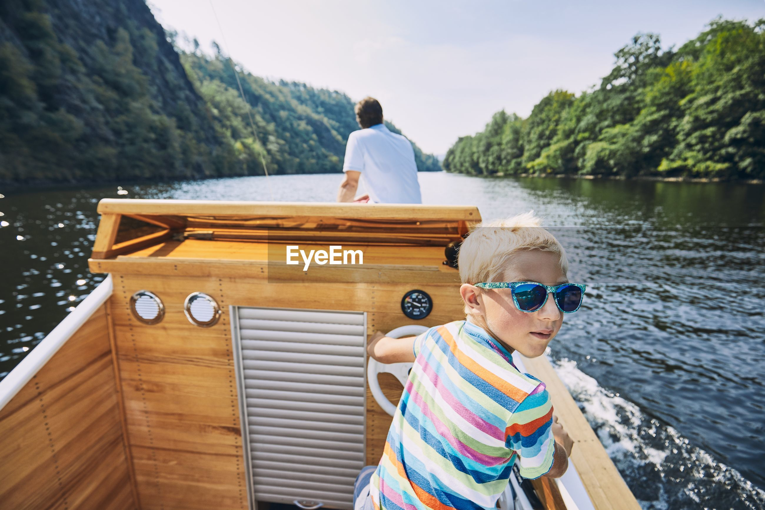 Portrait of boy wearing sunglasses on boat sailing in river