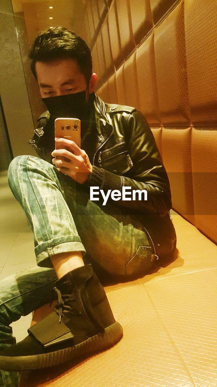 Man Wearing Mask Holding Mobile Phone On Floor