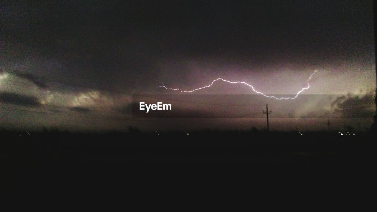 lightning, thunderstorm, power in nature, storm, weather, dramatic sky, forked lightning, cloud - sky, storm cloud, night, sky, nature, beauty in nature, silhouette, scenics, landscape, outdoors, no people, field, illuminated