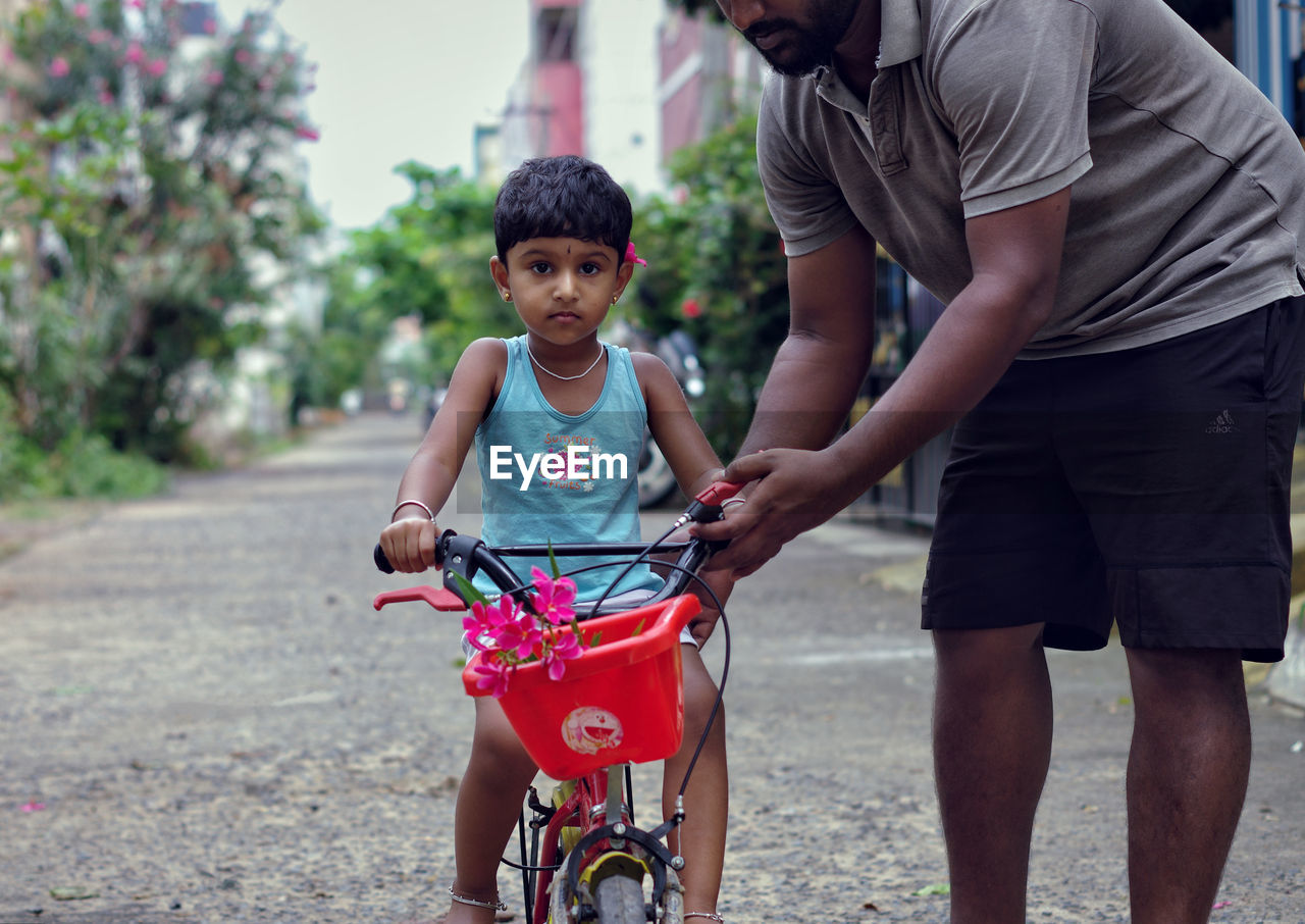Midsection Of Father Teaching Cycling To Daughter On Road
