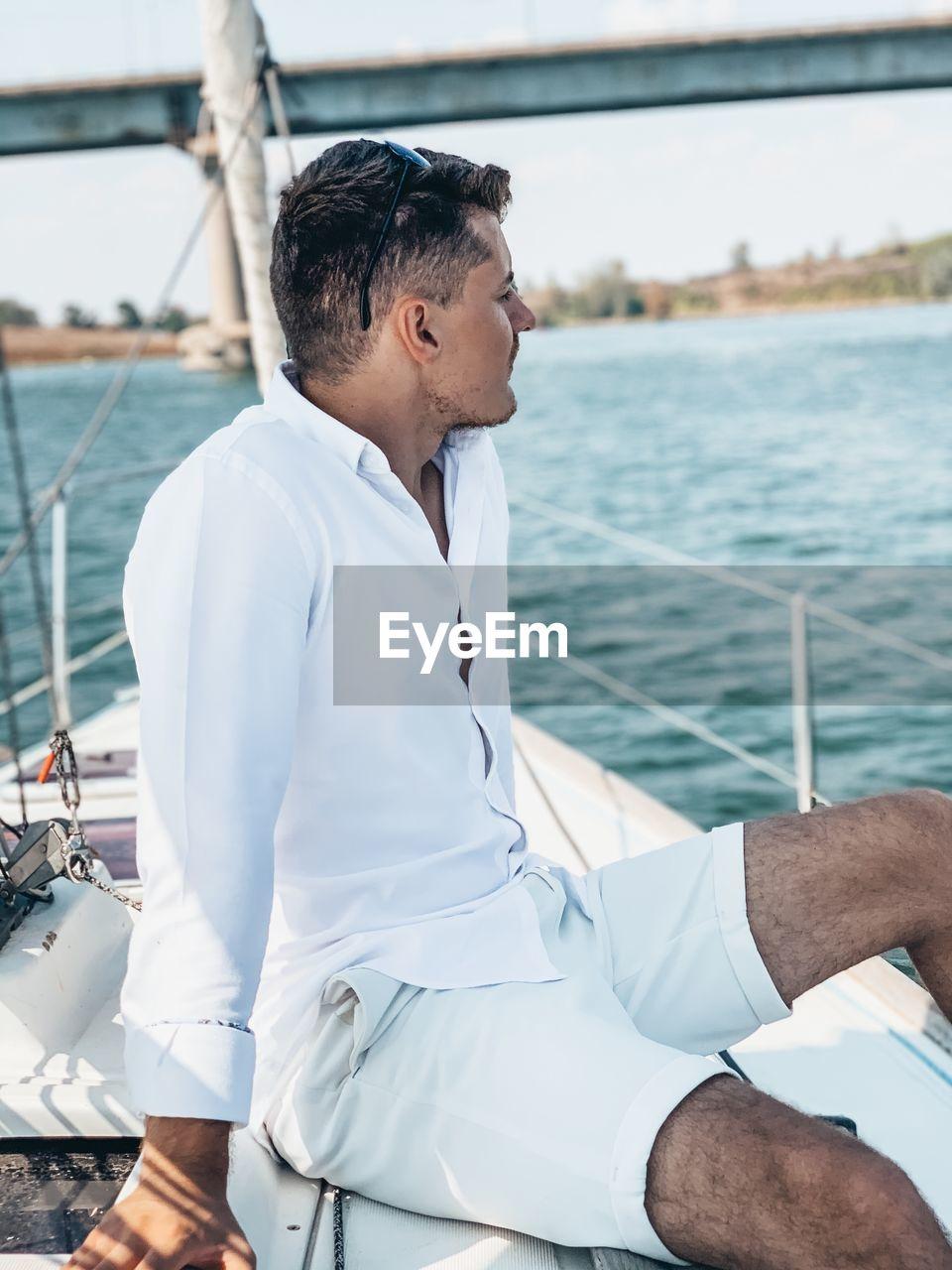 Man sitting on yacht in sea against bridge