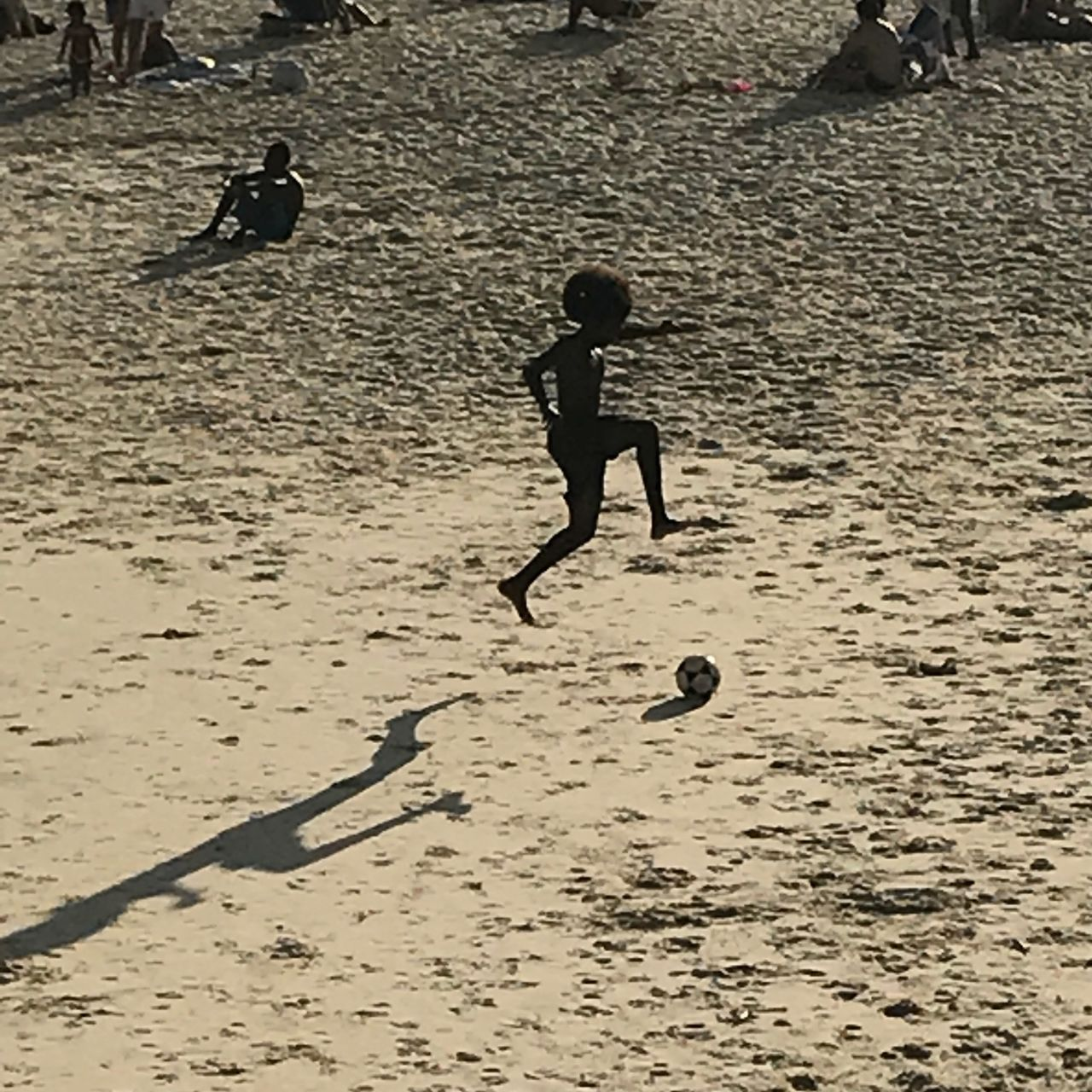 real people, child, men, full length, childhood, males, playing, one person, boys, leisure activity, lifestyles, shadow, ball, land, soccer ball, sand, soccer, nature, running, outdoors