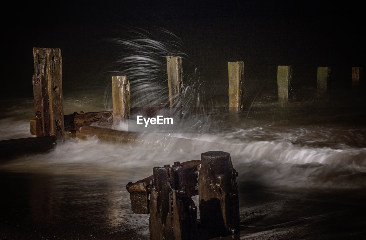 Water Flowing Through Old Wooden Posts