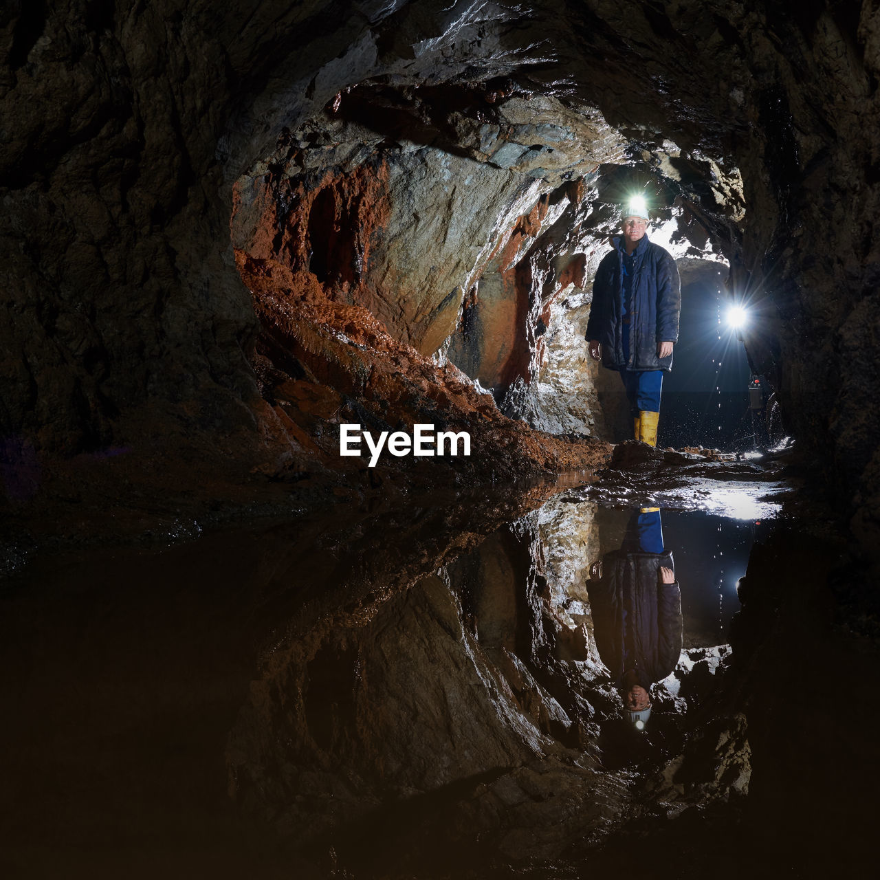 Man With Illuminated Headlamp Standing In Cave