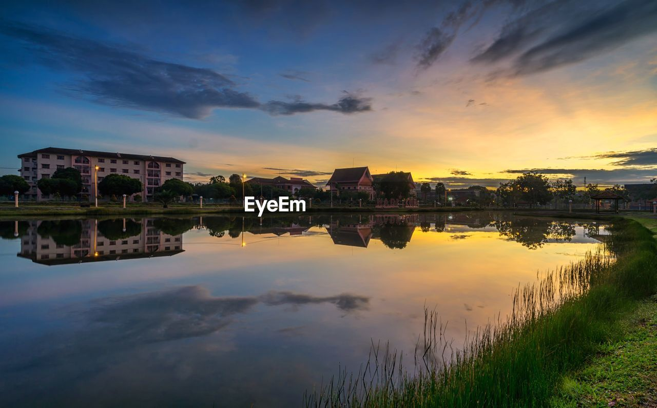 sky, water, reflection, sunset, cloud - sky, built structure, architecture, building exterior, lake, nature, waterfront, scenics - nature, beauty in nature, orange color, no people, tranquility, building, plant, outdoors, reflection lake