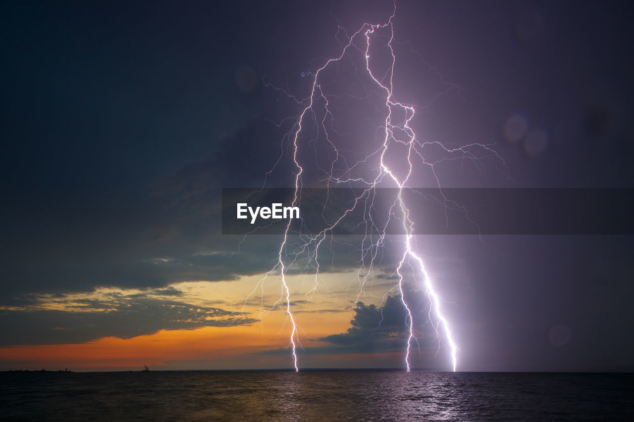 Forked Lightning Over Sea Against Sky During Sunset