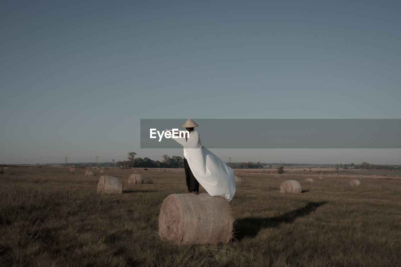Young man holding fabric while standing on hay bale at agricultural landscape