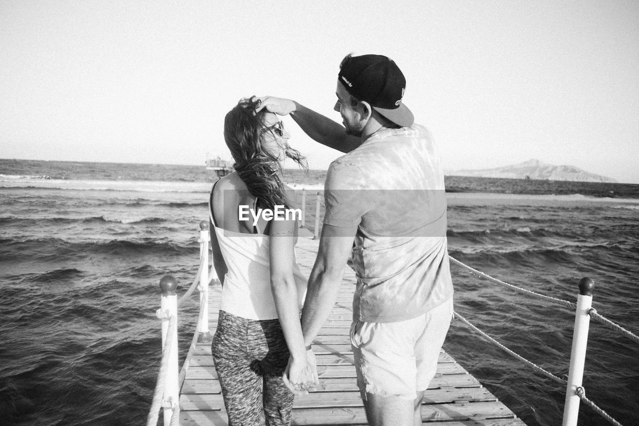 sea, two people, togetherness, real people, love, leisure activity, standing, water, men, bonding, nature, lifestyles, vacations, clear sky, couple - relationship, women, outdoors, embracing, beach, day, horizon over water, scenics, beauty in nature, sky, young women, friendship, young adult, adult, people