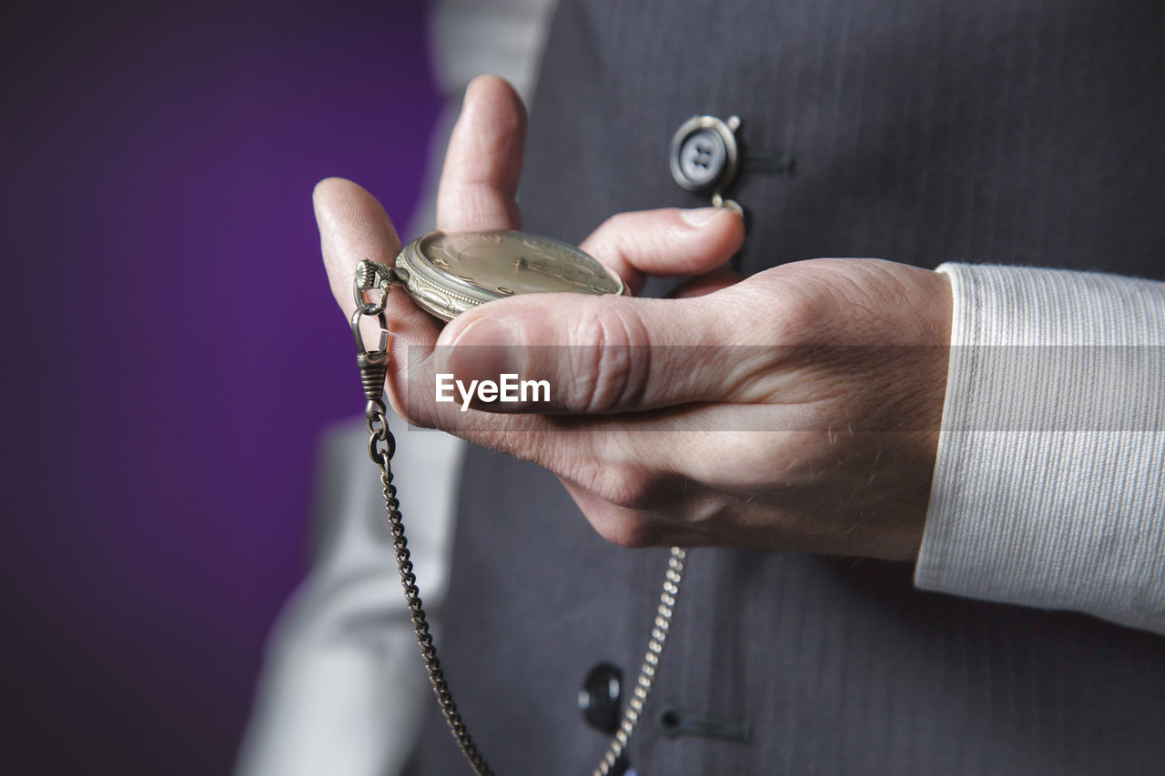 Midsection of businessman holding pocket watch