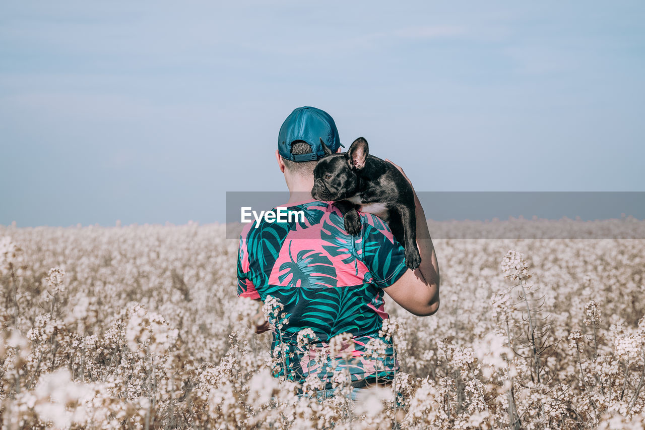 Man with dog standing by blooming flowers