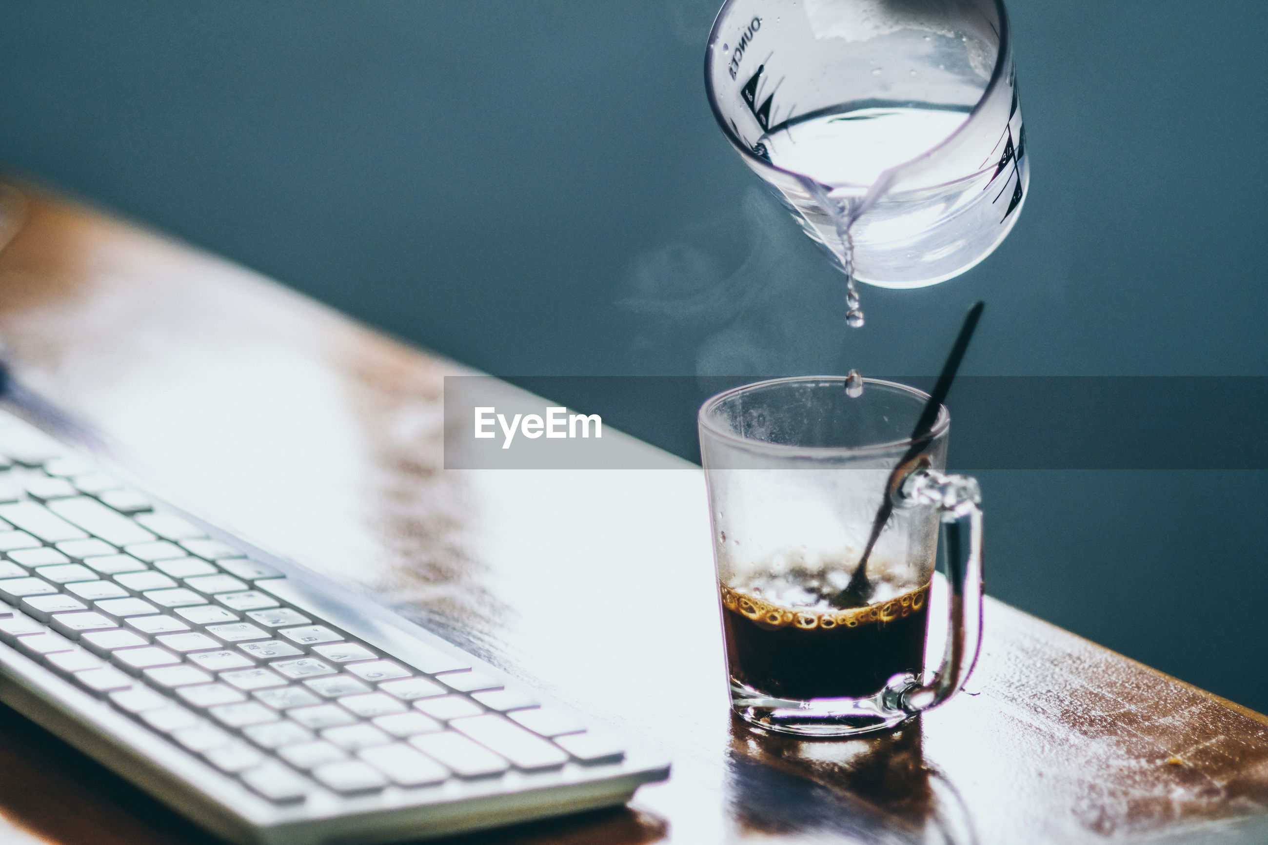 Water pouring in coffee cup by keyboard on table