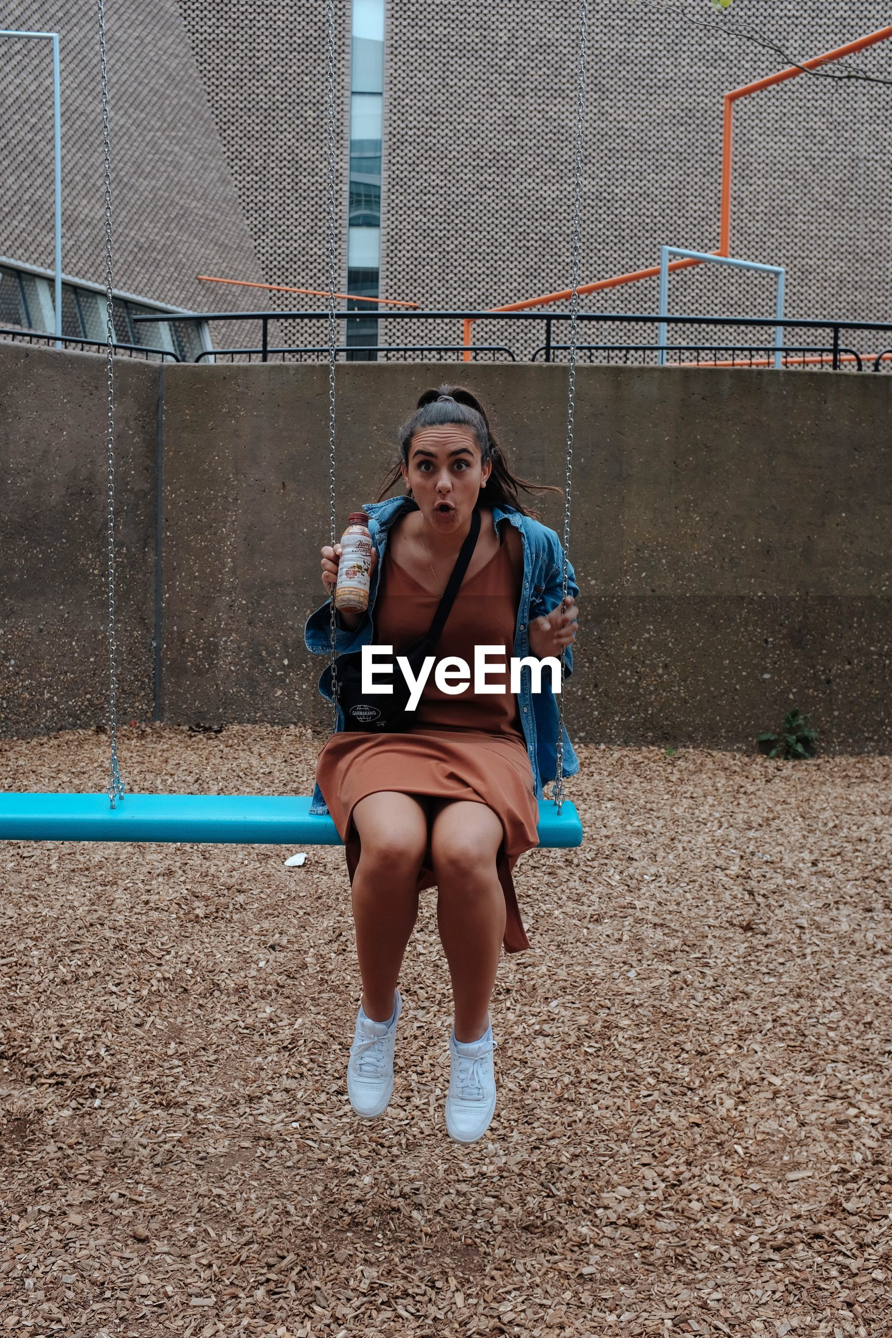 Full length portrait of shocked woman sitting on swing in playground