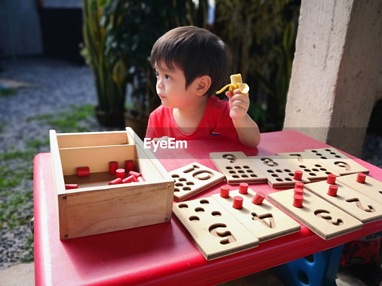 Cute boy playing with toys on table