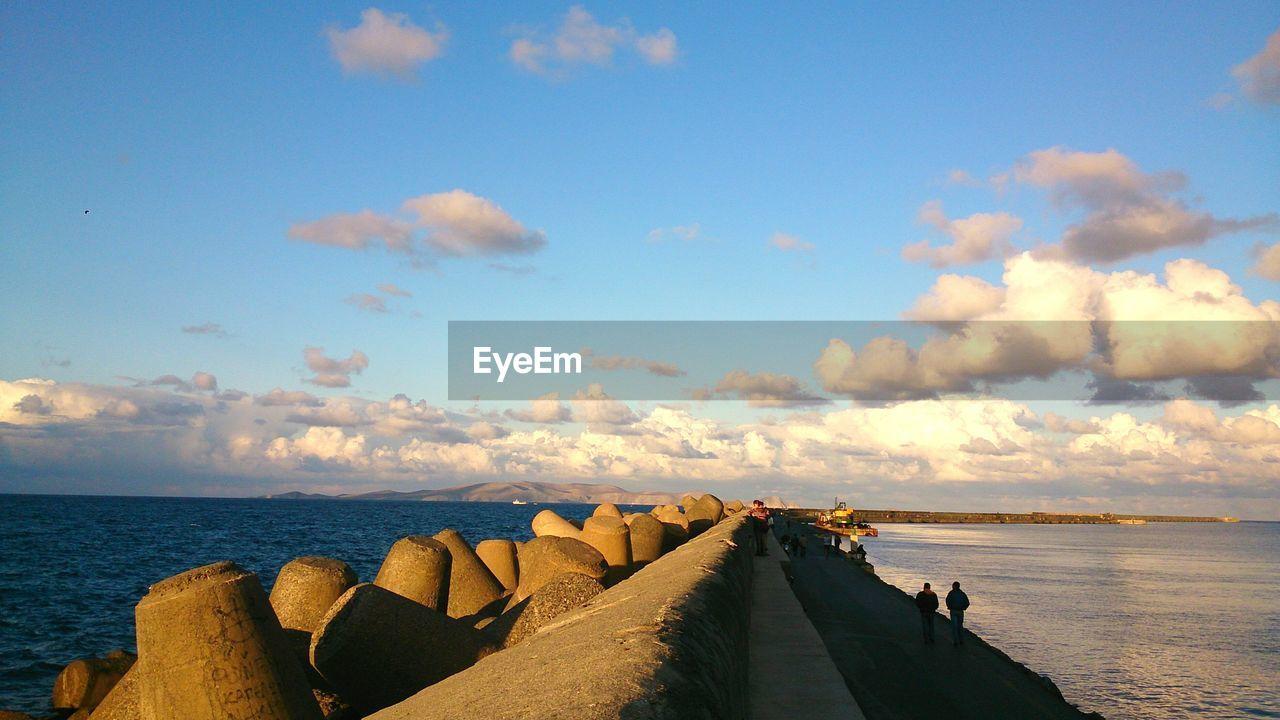 People walking on pier by groyne rocks in sea against sky