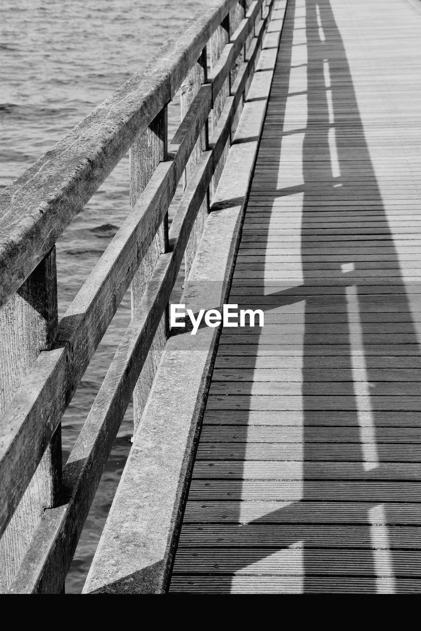 water, shadow, day, high angle view, nature, no people, sunlight, outdoors, architecture, wood - material, footpath, the way forward, pattern, pier, diminishing perspective, built structure, direction, empty, railing, wood paneling, long, concrete, focus on shadow